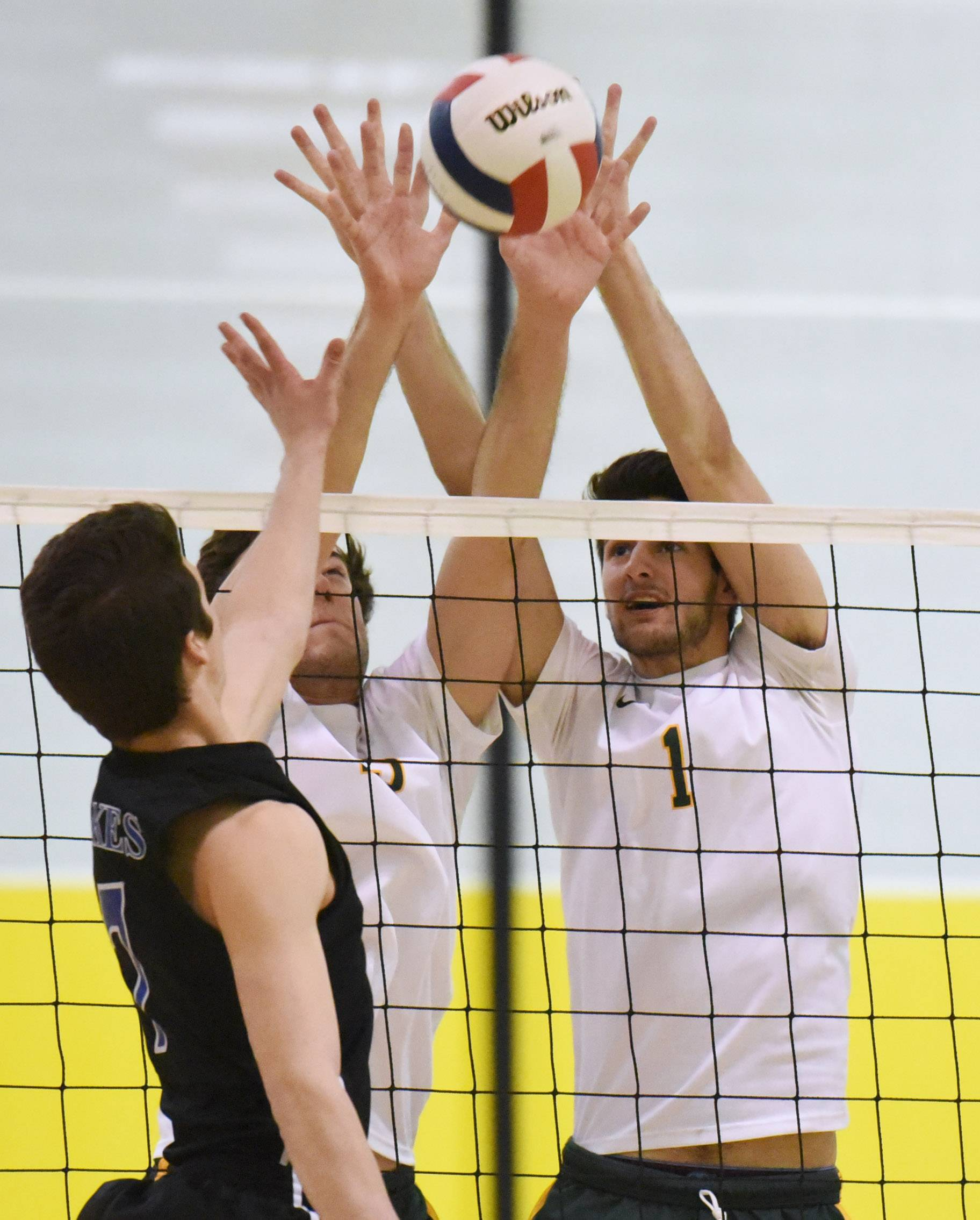 Stevenson's Hudson Havenhill, center, and Matthew Cliffer (1) block a shot by Lakes' Jacob Keenan during Monday night's boys volleyball matchup in Lincolnshire.