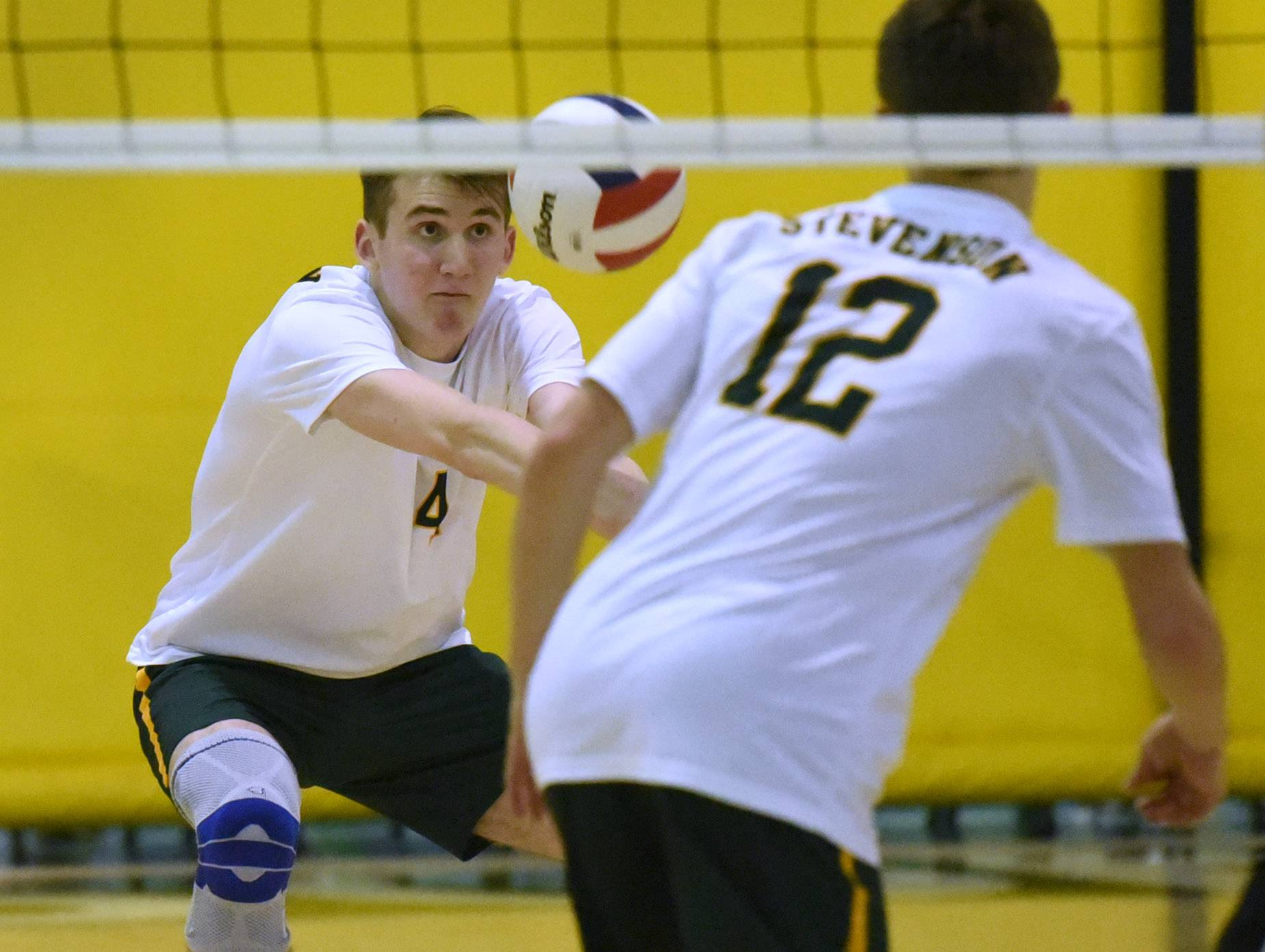 Stevenson's Grant Maleski, left, digs the ball during Monday night's boys volleyball match against Lakes in Lincolnshire.