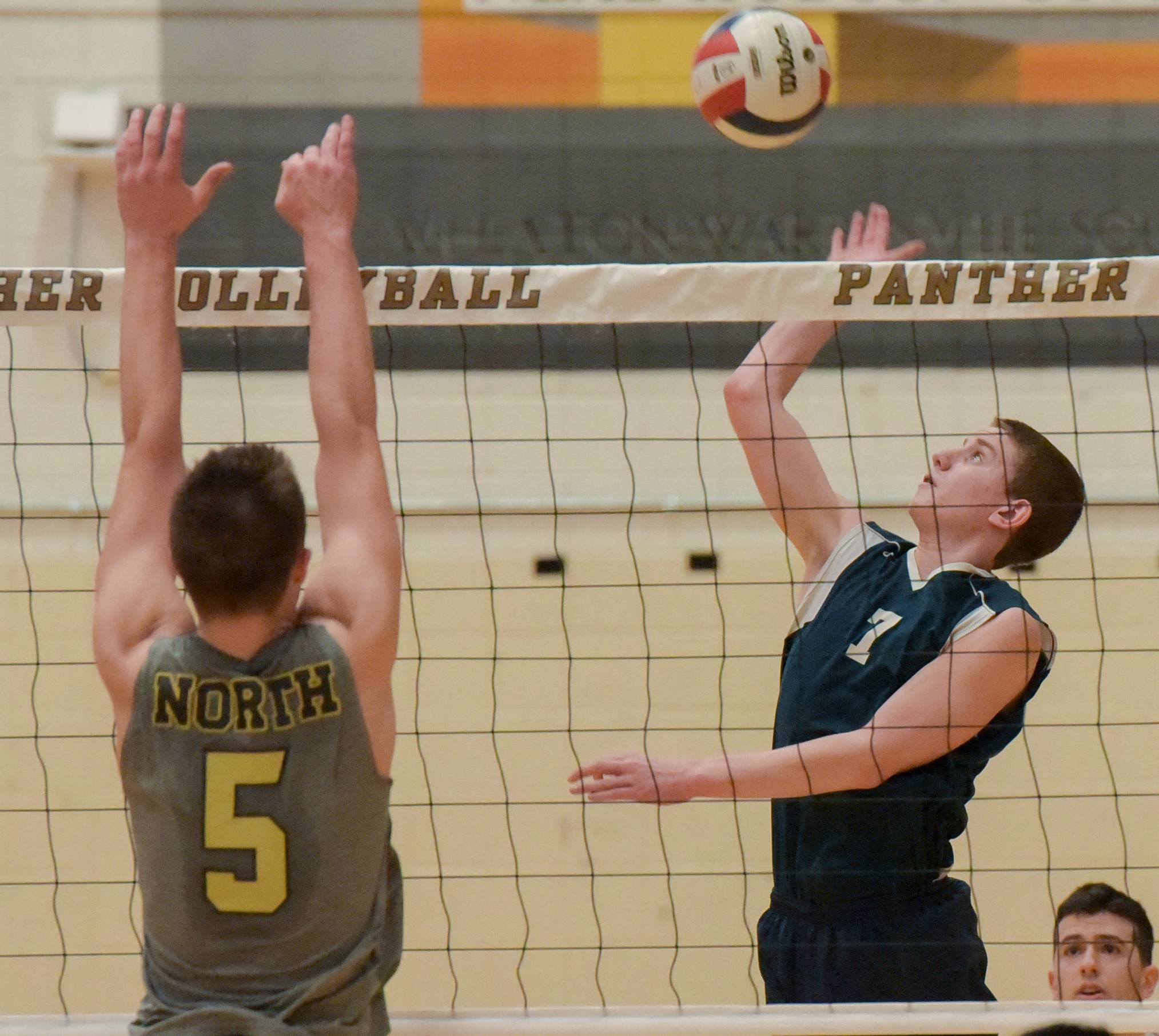 Addison Trail's Michael Strycharz sets up to fire one past Glenbard North's Trent Weber during varsity boys volleyball Monday in Carol Stream.
