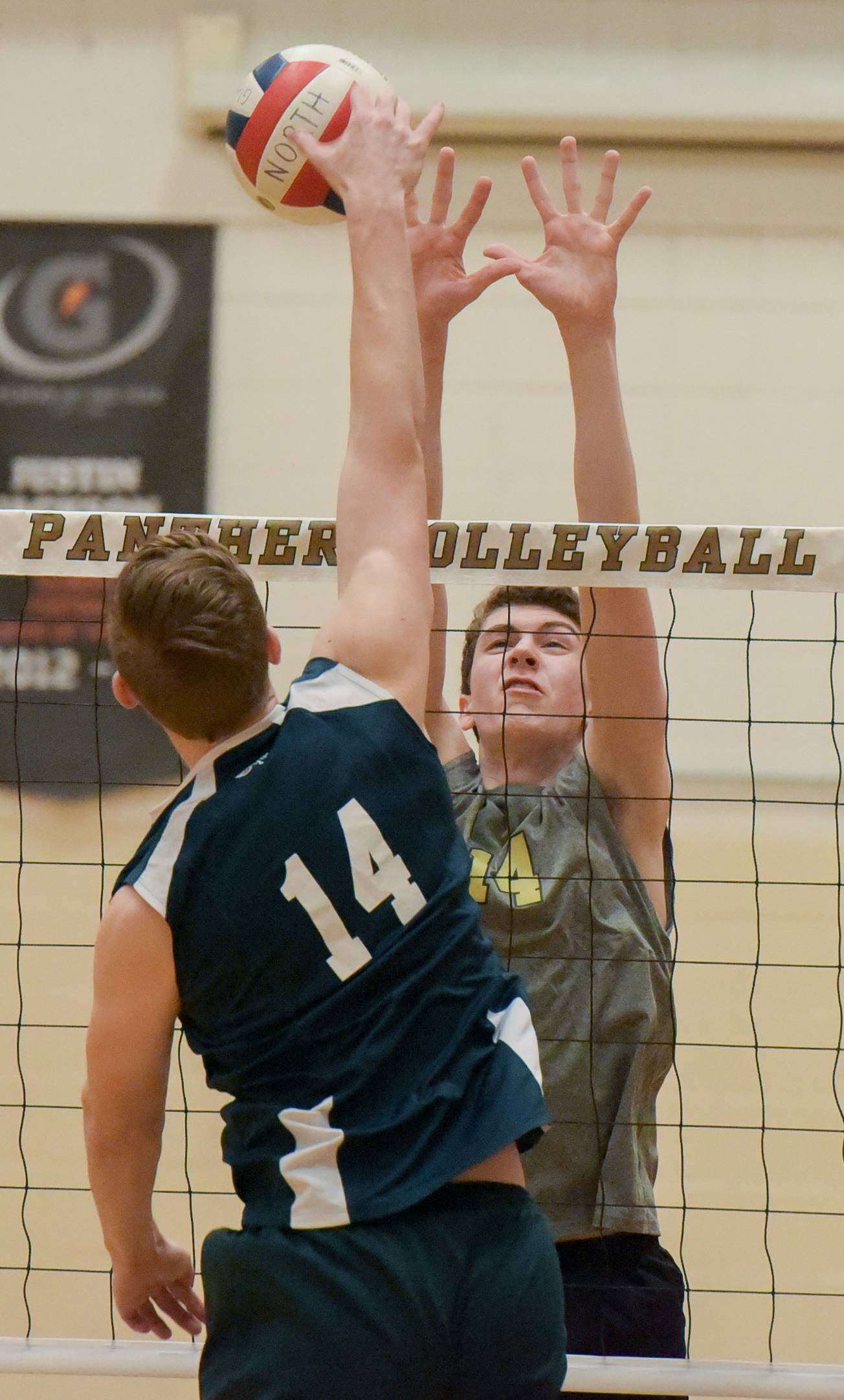 Addison Trail's Michael Pudlo hit one over the net as Glenbard North's Ian Krohn leaps to block the shot during varsity boys volleyball Monday in Carol Stream.