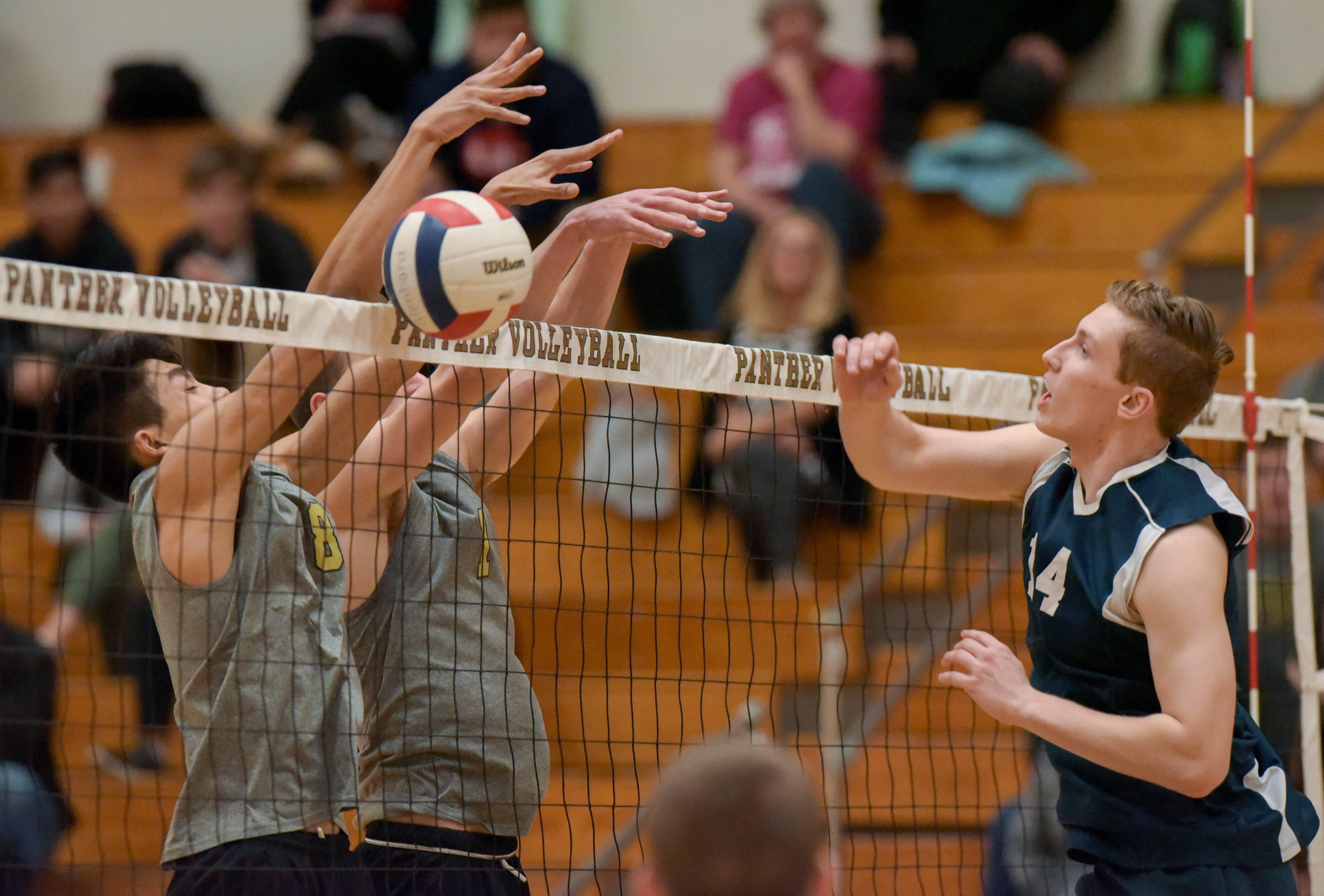 Glenbard North's Bryan Nguyen and Eric Tripp block a shot by Addison Trail's Michael Pudlo during varsity boys volleyball Monday in Carol Stream.