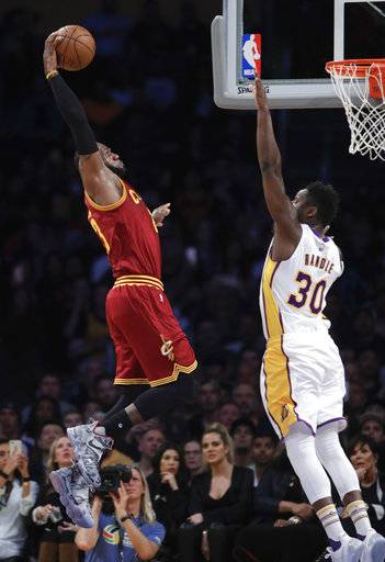 Cleveland Cavaliers' LeBron James, left, goes up for a dunk under defense by Los Angeles Lakers' Julius Randle during the first half of an NBA basketball game Sunday, March 19, 2017, in Los Angeles.