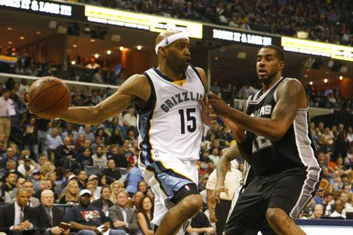 Memphis Grizzlies' Vince Carter (15) passes while being defended by San Antonio Spurs' LaMarcus Aldridge (12) in the first half of an NBA basketball game Saturday, March 18, 2017, in Memphis, Tenn.