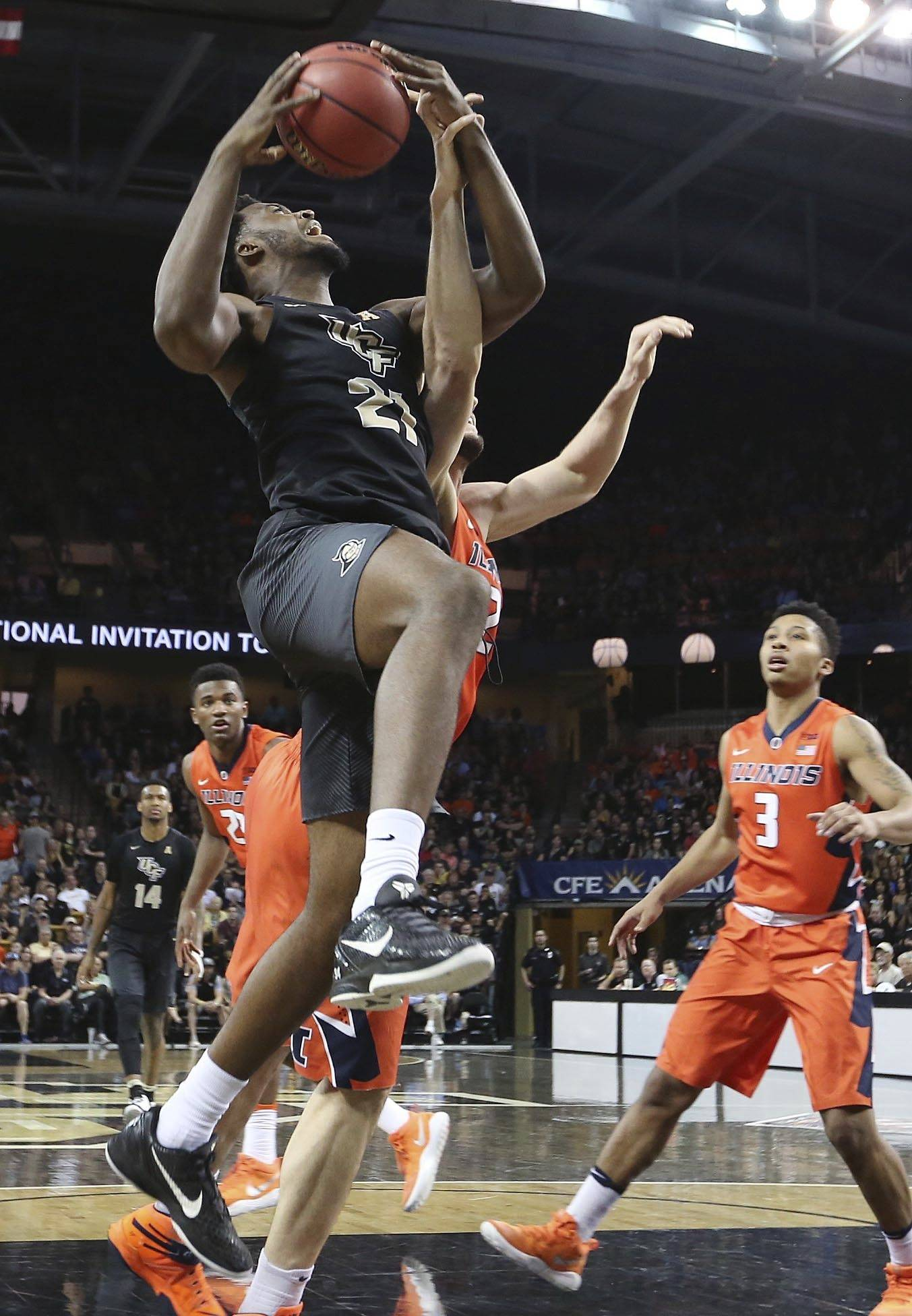 Central Florida forward Chad Brown (21) scores over Illinois defenders including guard Te'Jon Lucas (3) during an NCAA college basketball game of the NIT in Orlando, Fla., Wednesday, March 22, 2017. (Stephen M. Dowell/Orlando Sentinel via AP)