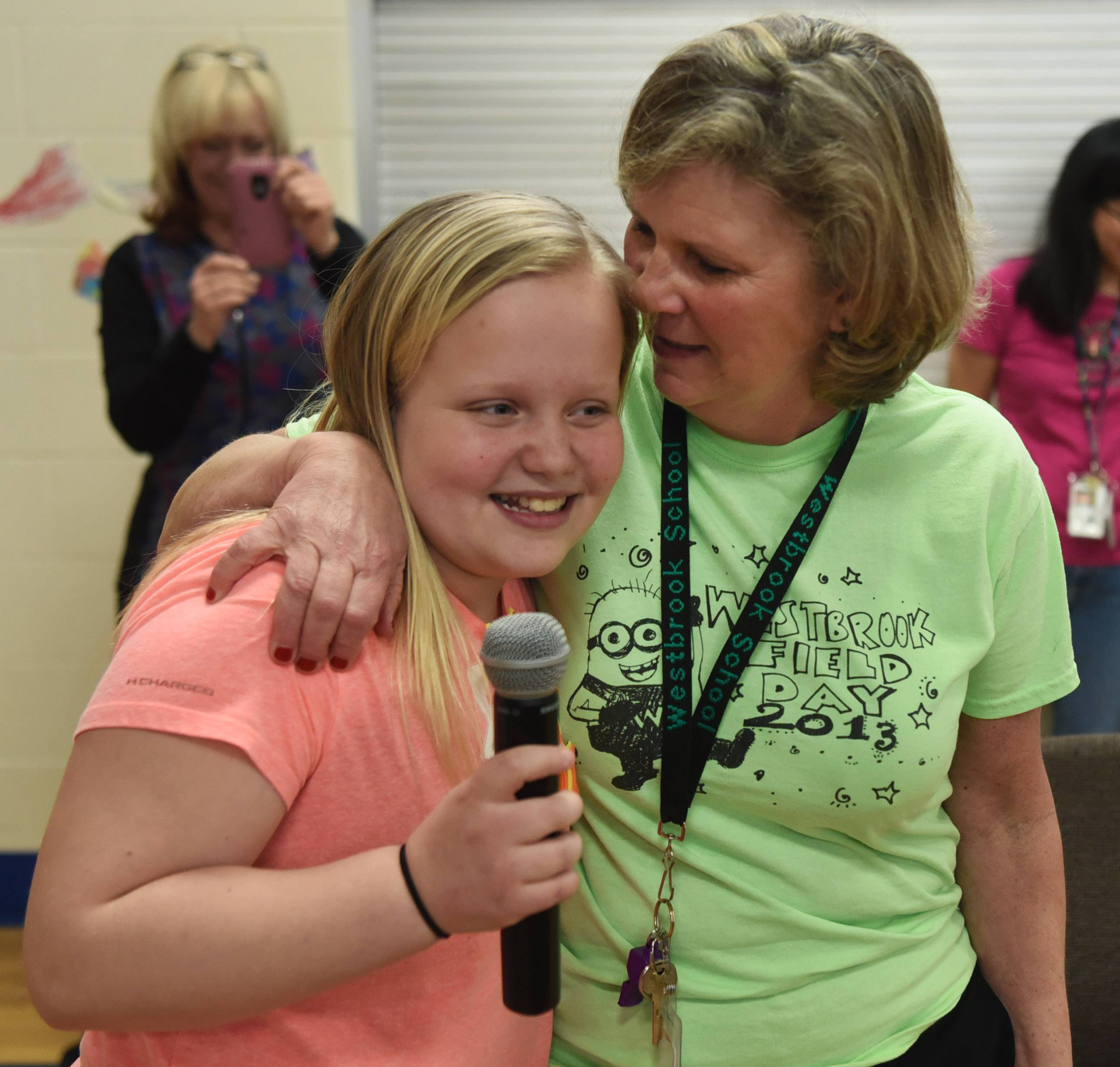 "Abigail Valpatic, 10, gets a hug after singing ""You are my Sunshine"" to her former teacher, Westbrook School PE teacher Lori Many, who will be retiring at the end of the school year. In addition to the visit by Valpatic, who is now a fifth grader at Fairview School in Mount Prospect, Many was surprised with a flash mob of kindergarten and first-grade students at Westbrook Friday."