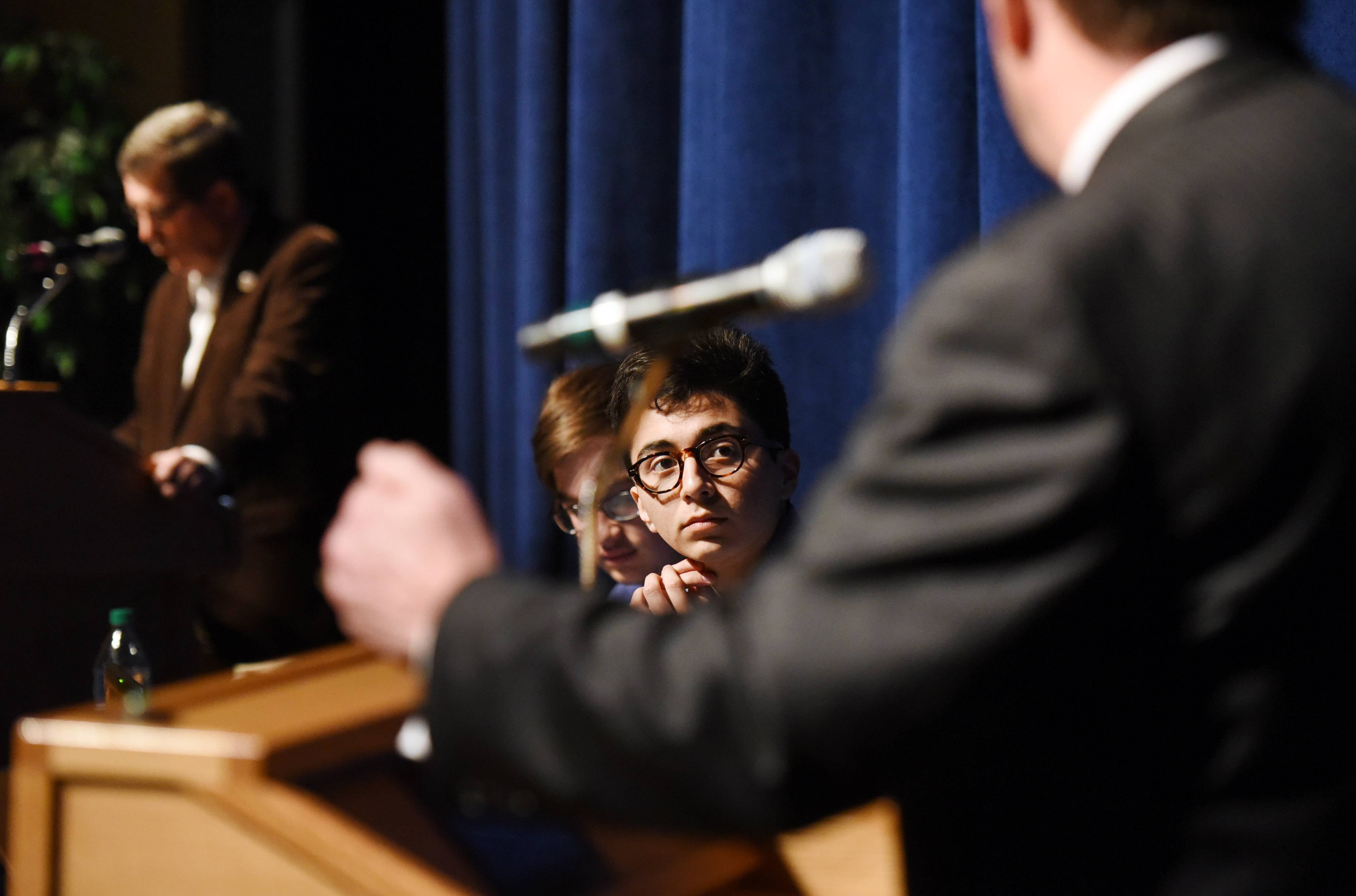 Libertyville High School students Jack Kosowski, second from left, and Alejandro Garcia Escobar listen to Libertyville mayoral candidates Terry Weppler, left, and Jeff Harger during a student-led town hall meeting Friday.