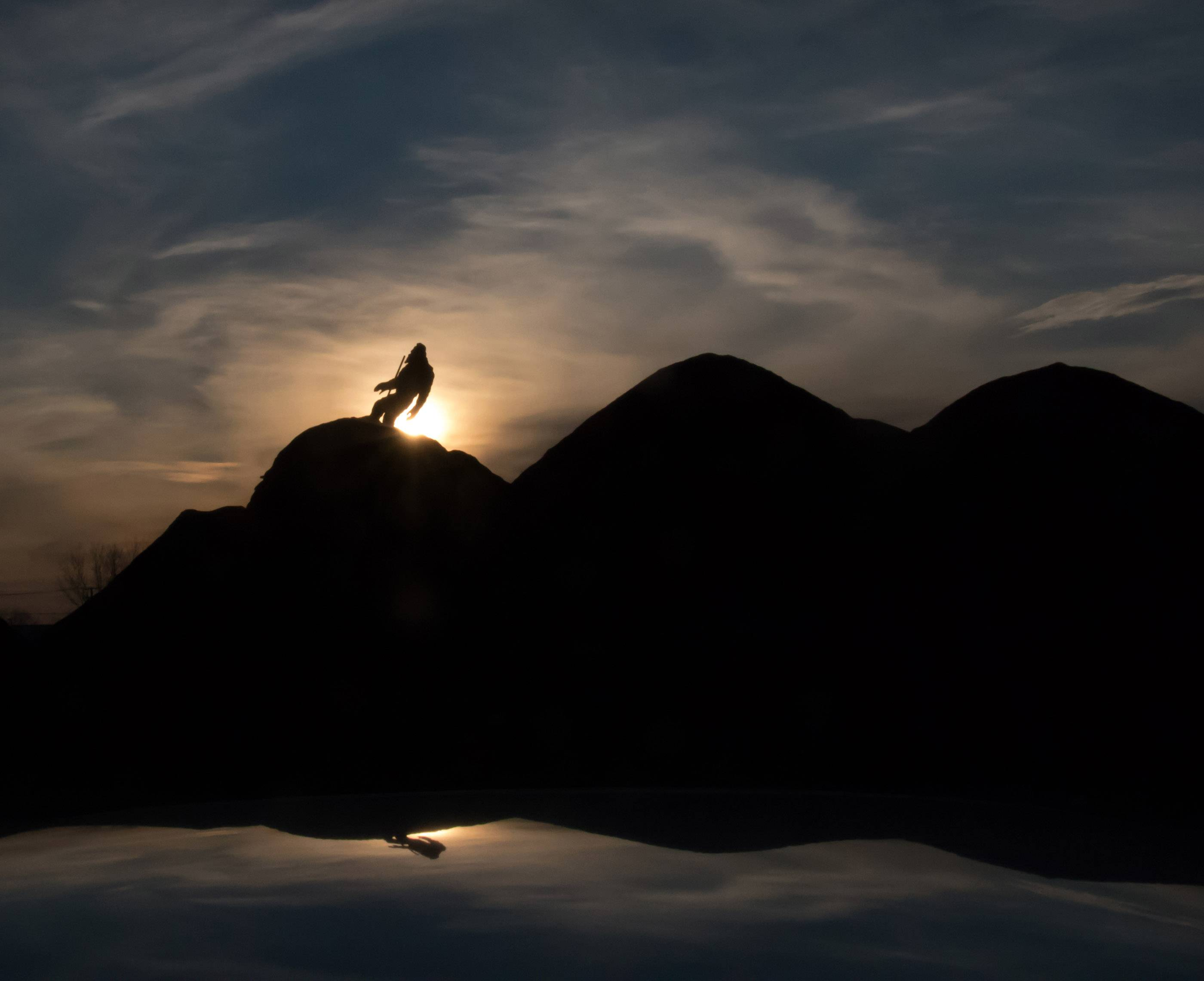 A figure appears on top of a mulch pile on Higgins Road at sunset, as reflected on the hood of a car.