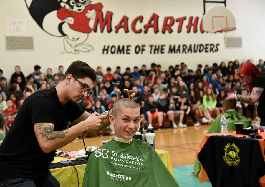 Seventh-grader Alex Jelaca gets a buzz cut from Matthew Crispin of Gentlemen's Row Barber Shop in Des Plaines on Friday at MacArthur Middle School. Prospect Heights Elementary District 23 hosted the fundraiser for the St. Baldrick's Foundation.
