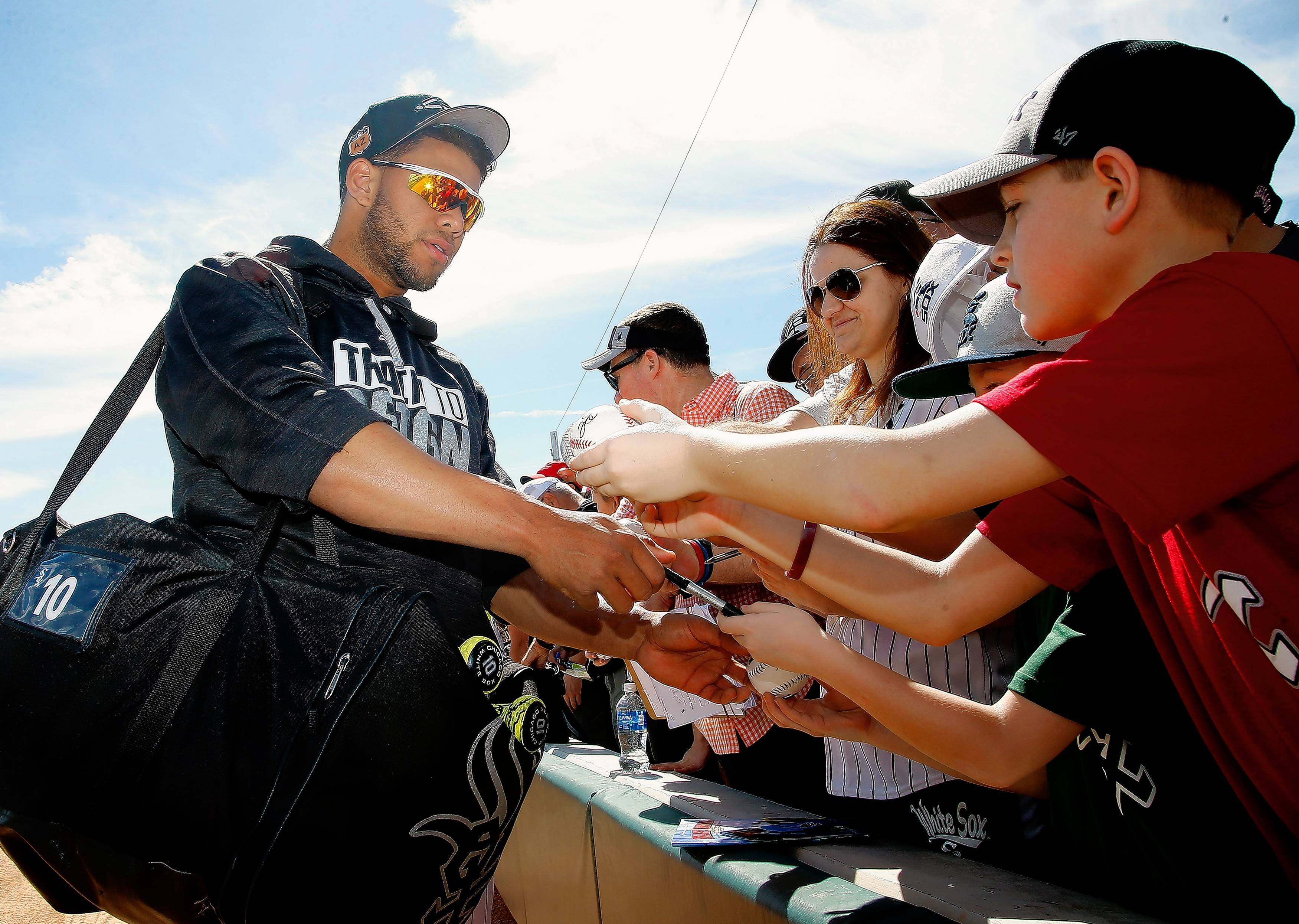Chicago White Sox second baseman Yoan Moncada signs autographs for fans prior to a spring training baseball game against the Los Angeles Angels Saturday, March 4, in Glendale, Ariz.