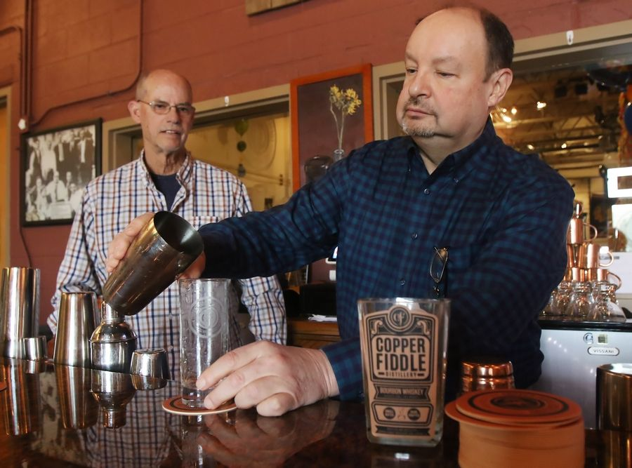 Copper Fiddle Distillery owner Jose Hernandez pours a drink with co-owner Fred Robinson at the bar. They're hopeful about pending state legislation that would allow them to bypass distributors and self-deliver some of their own products.