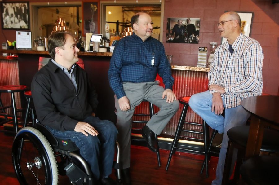 State Sen. Dan McConchie of Hawthorn Woods, left, discusses his bill to help craft distilleries with Copper Fiddle Distillery owners Jose Hernandez and Fred Robinson in Lake Zurich.