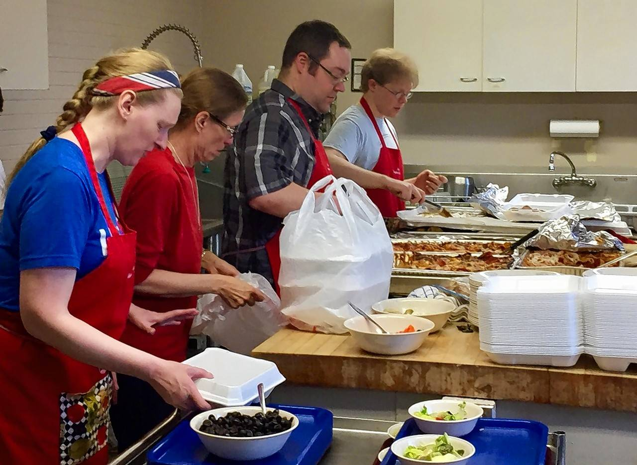 Volunteers at St. Charles Episcopal Church fill carryout containers Sunday with a free pasta meal. The church is marking eight years of serving free pasta dinners on the last Sunday of each month.