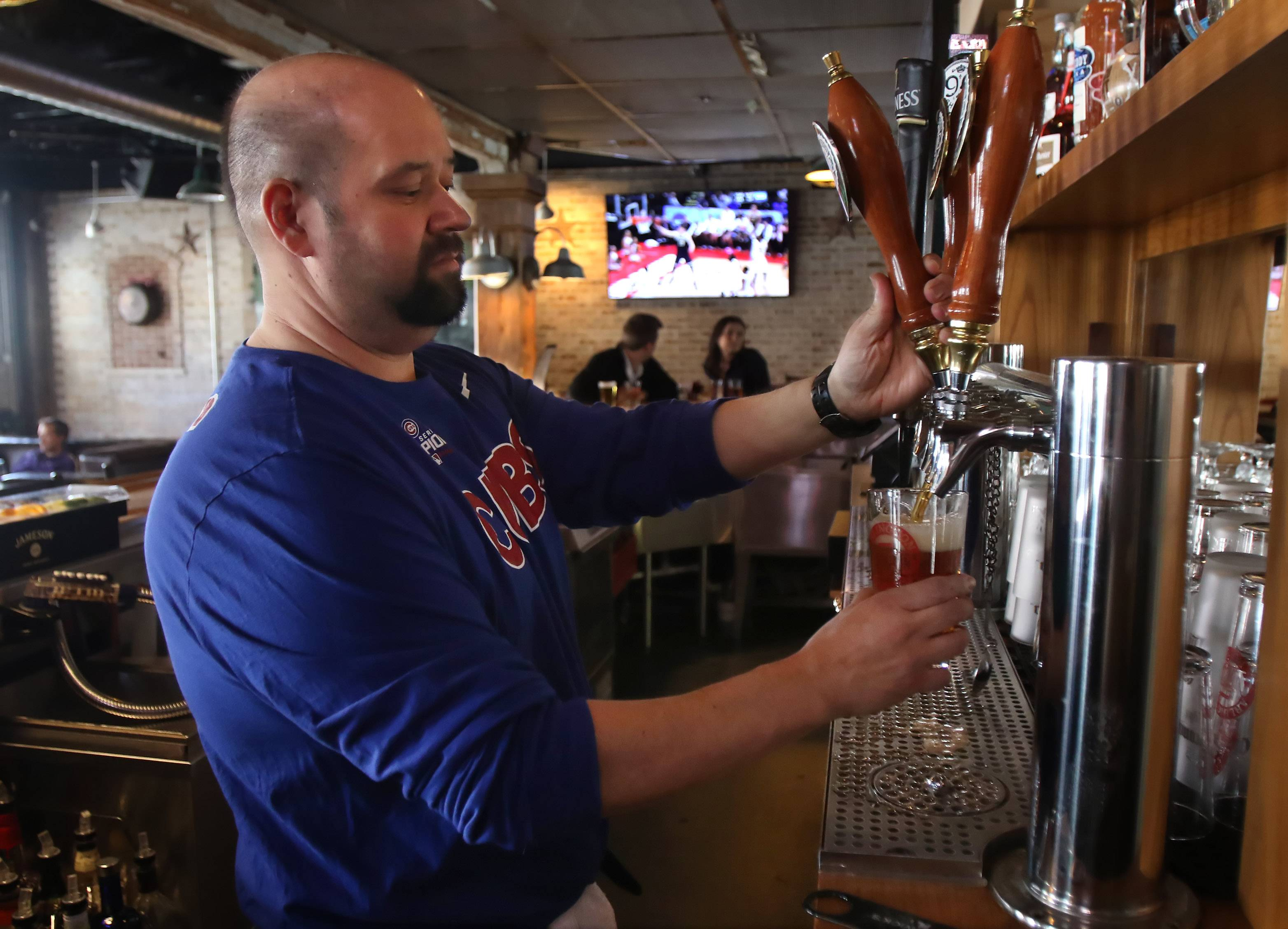 Bartender John Polihronis pours a beer at the Arlington Ale House in Arlington Heights.