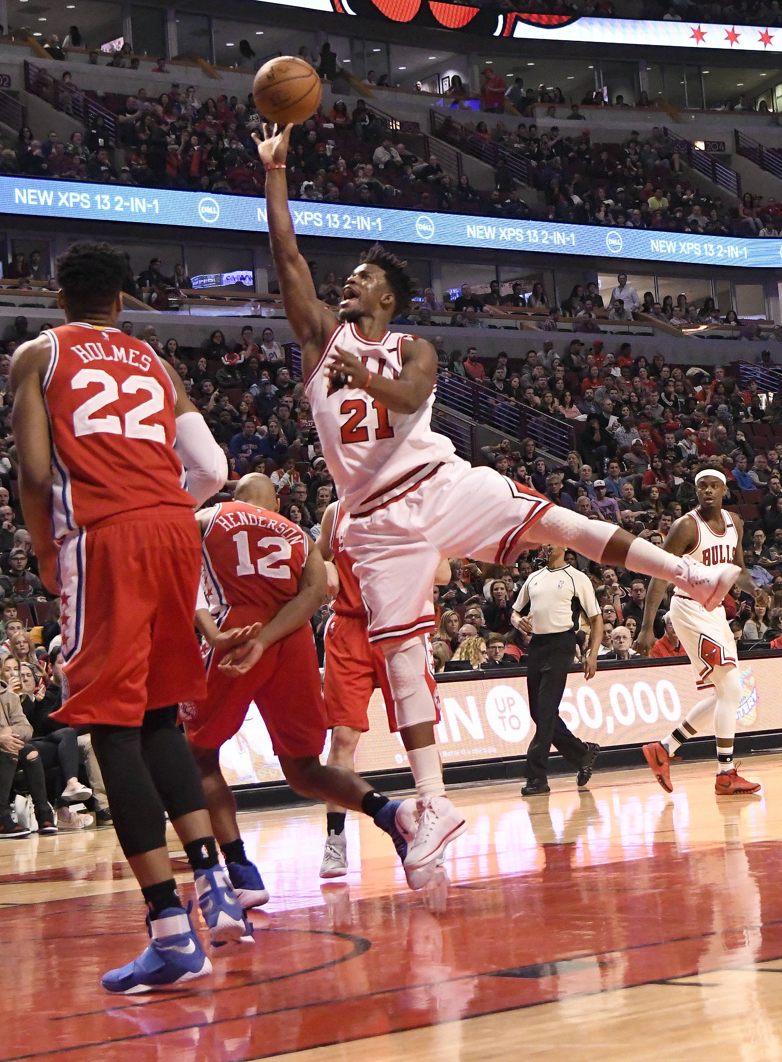 Chicago Bulls forward Jimmy Butler (21) shoots over Philadelphia 76ers guard Gerald Henderson (12) and forward Richaun Holmes (22) during the second half of an NBA basketball game in Chicago, Friday, March 24, 2017. (AP Photo/David Banks)