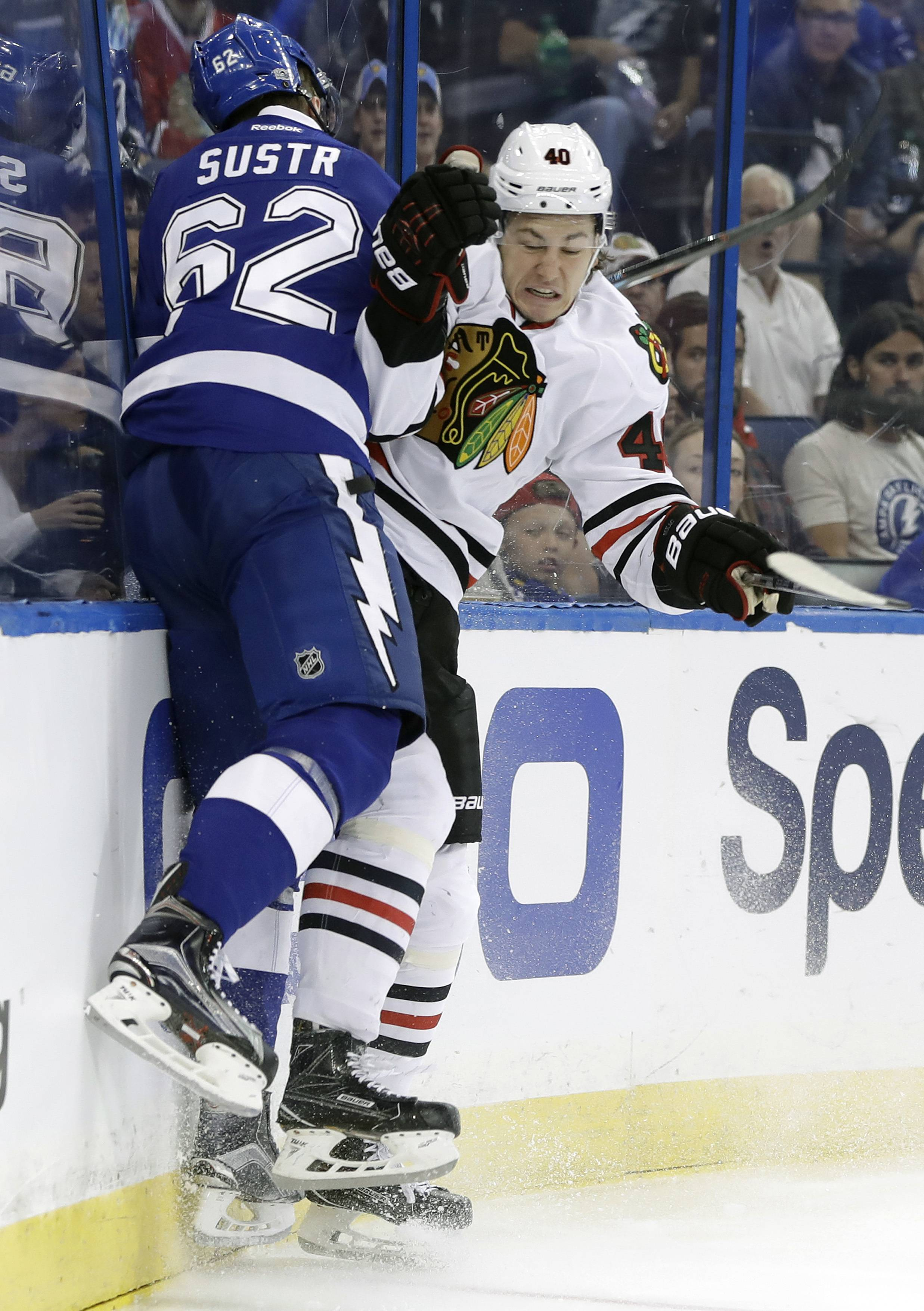 Chicago Blackhawks center John Hayden (40) slams Tampa Bay Lightning defenseman Andrej Sustr (62) into the boards during the first period of an NHL hockey game, Monday, March 27, 2017, in Tampa, Fla. (AP Photo/Chris O'Meara)