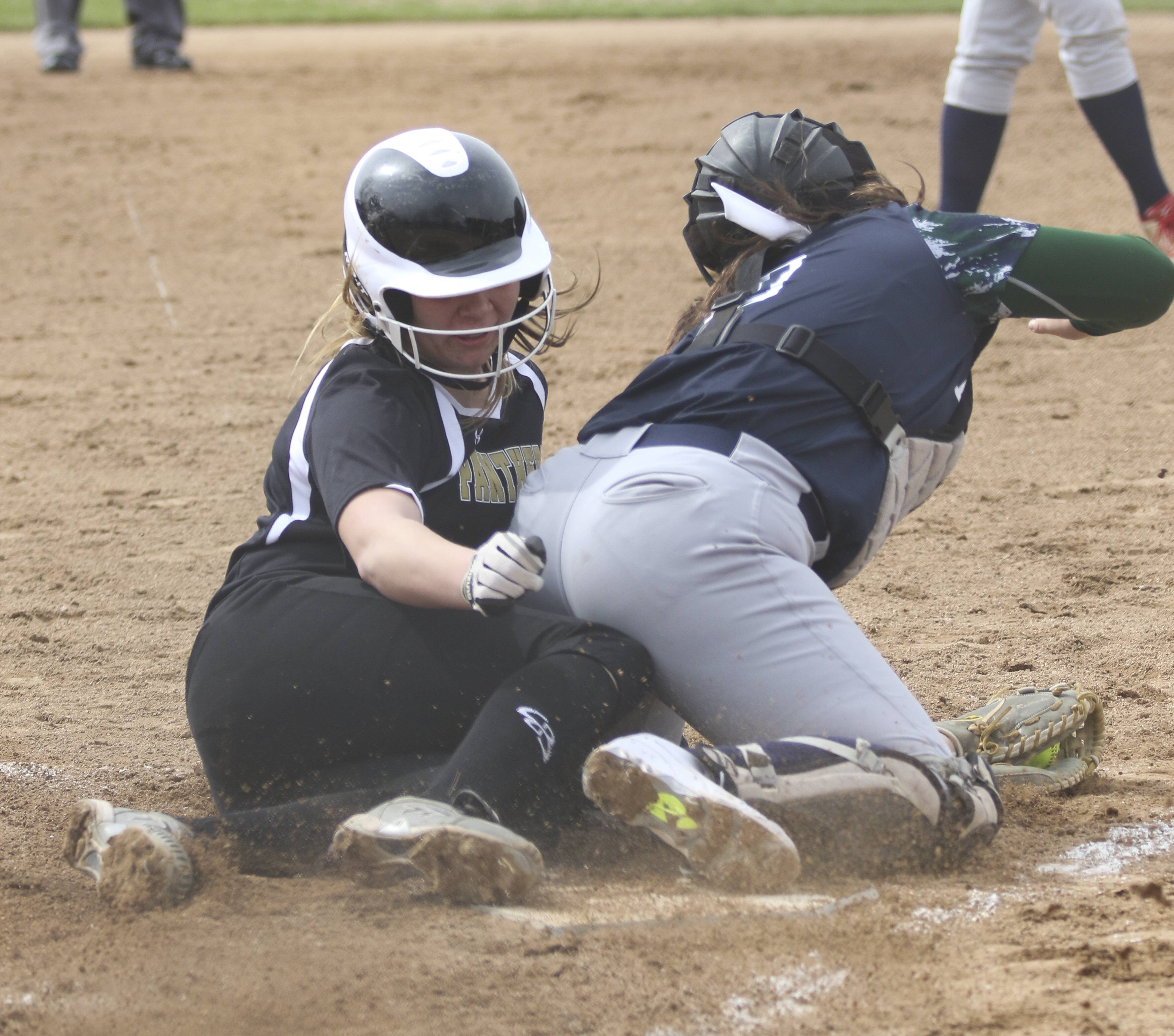 Glenbard North's Kaitlyn Schietler collides with Bartlett catcher Taylor Rotondo at home plate in the first inning during softball on Wednesday in Carol Stream.