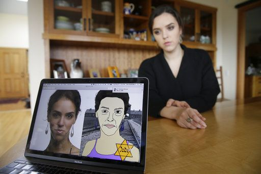 In this Feb. 21, 2017, photo, Erin Schrode poses behind a laptop displaying anti-Semitic images of herself that she received in her email and social media at her home in Mill Valley, Calif. Less than a week before the election for her long-shot congressional campaign, Schrode woke up in her northern California home, rolled over in bed and reflexively checked her cellphone. The 25-year-old activist burst into tears when she found a barrage of anti-Semitic emails.