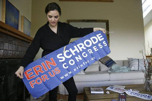 In this Feb. 21, 2017, photo, Erin Schrode unfurls a campaign banner at her home in Mill Valley, Calif. Less than a week before the election for her long-shot congressional campaign, Schrode woke up in her northern California home, rolled over in bed and reflexively checked her cellphone. The 25-year-old activist burst into tears when she found a barrage of anti-Semitic emails.