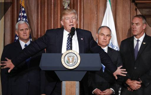 FILE - In this Tuesday, March 28, 2017 file photo, President Donald Trump, accompanied by from left, Vice President Mike Pence, Environmental Protection Agency (EPA) Administrator Scott Pruitt, and Interior Secretary Ryan Zinke, speaks at EPA headquarters in Washington, prior to signing an Energy Independence Executive Order. Environmental groups are preparing to go to court to battle Trump's efforts to roll back his predecessor's plans to curb global warming. But they say their first order of business is to mobilize a public backlash against an executive order Trump signed on Tuesday that eliminates many restrictions of fossil fuel production. (AP Photo/Pablo Martinez Monsivais, File)