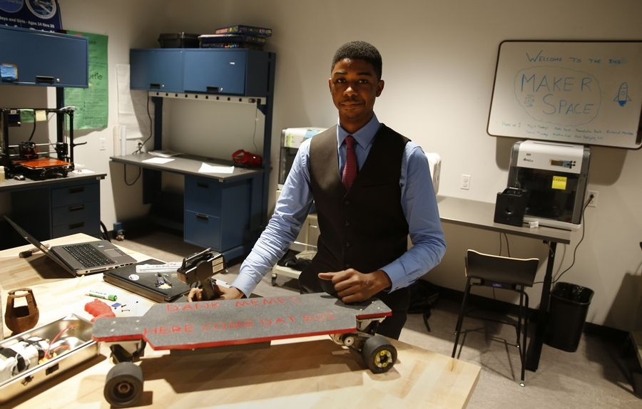 Illinois Math and Science Academy senior Malik Roberson stands behind an electric longboard he constructed in a new group collaboration space on the campus. The board can reach speeds of 22 mph, with some of its components made with a 3-D printer.
