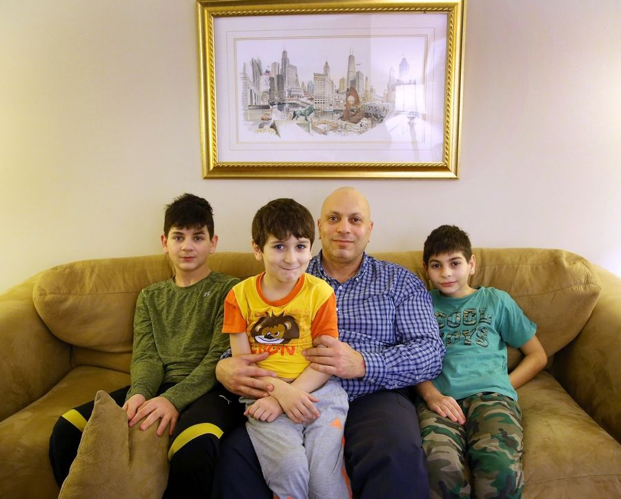 Syrian refugee Marwan Saffaf sits with his sons, from left, Homam, Eylas and Fares at their apartment in Des Plaines.