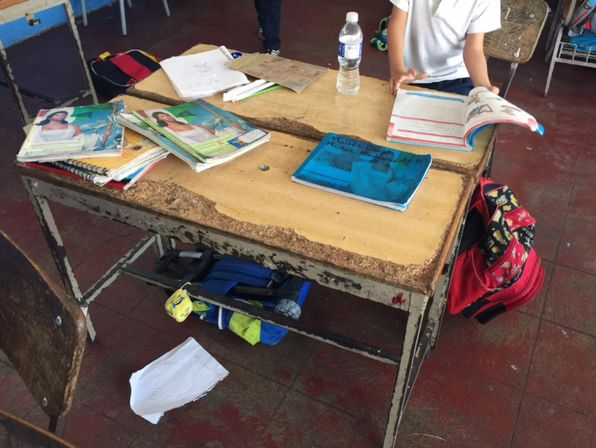 Elementary school students in Puerta Vallarta, Mexico work at desks that appear to be decades old.