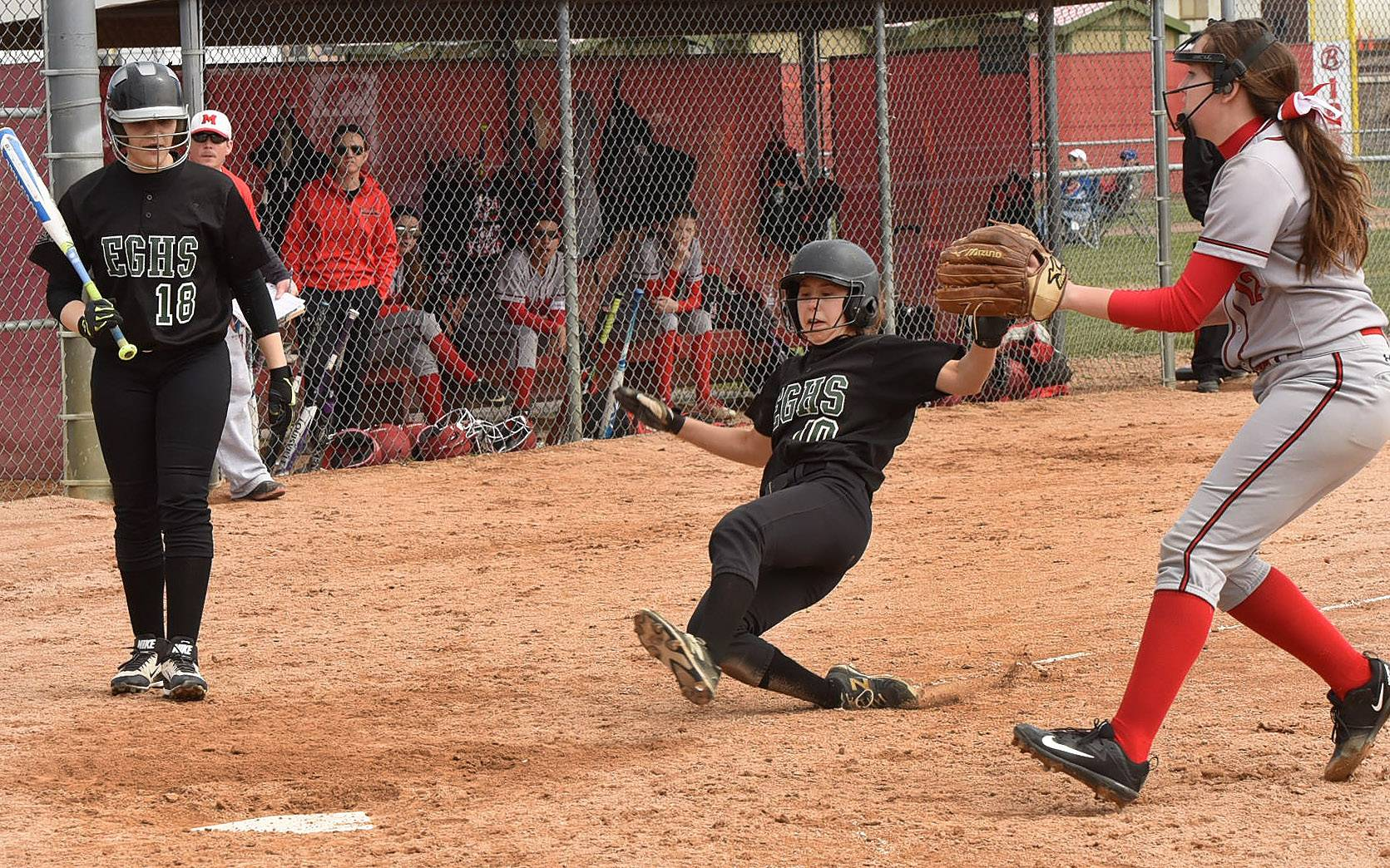 Elk Grove's Jessica Kearns scores on a wild pitch against Mundelein at Barrington's Fields of Dreams.
