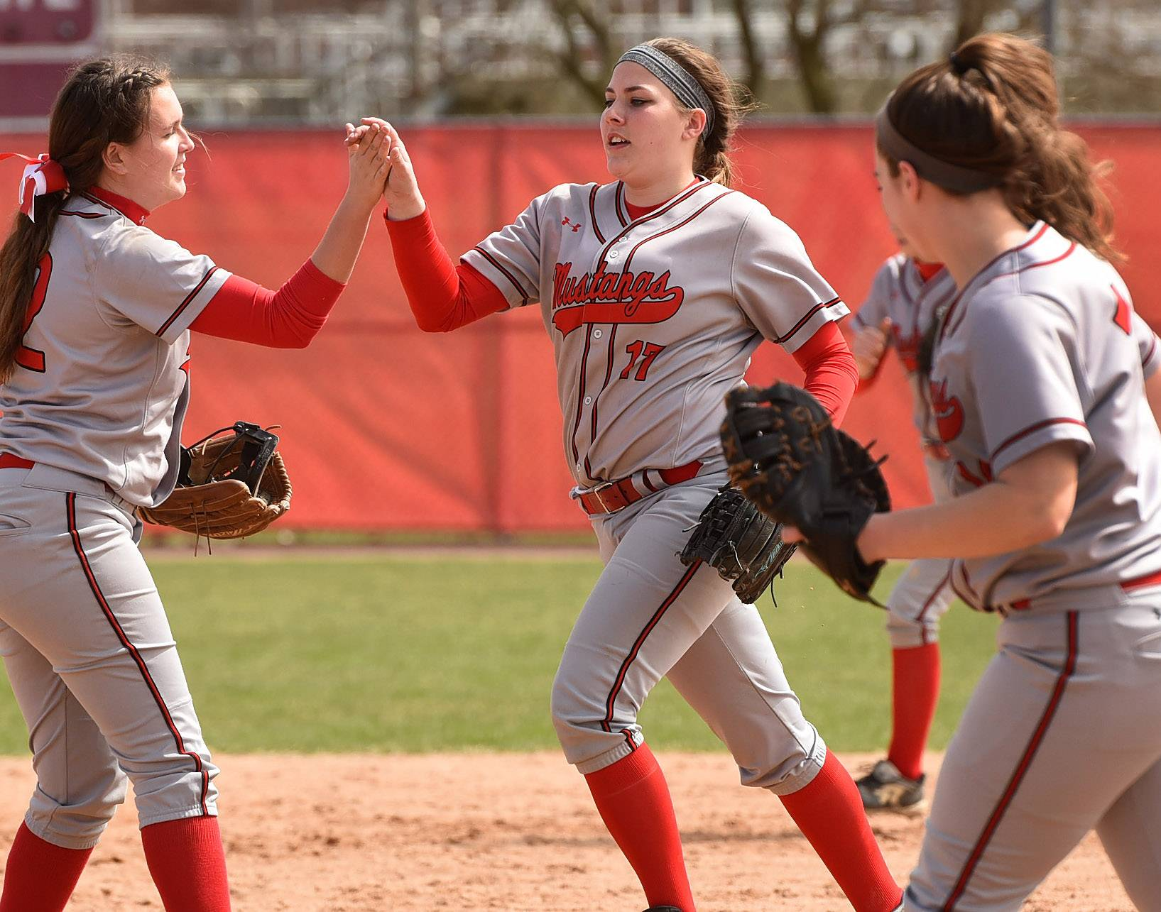 Mundelein's Breanna Adams is congratulated after forcing out Elk Grove's Sabra Morton during softball at Barrington's Fields of Dreams.