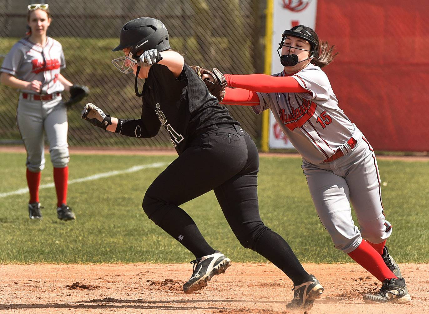Mundelein's Kira Buckner tags out Elk Grove's Jamie Klicka in a rundown during softball at Barrington's Fields of Dreams.