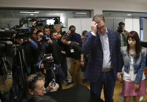 Current Serbian Prime Minister and presidential candidate Aleksandar Vucic, right, waits at a polling station with his daughter Milica, in Belgrade, Serbia, Sunday, April 2, 2017. Around 6.7 million voters in Serbia choose a new president in an election Sunday that will test the popularity of the dominant, populist prime minister, Aleksandar Vucic, against 10 beleaguered candidates from the fragmented opposition.
