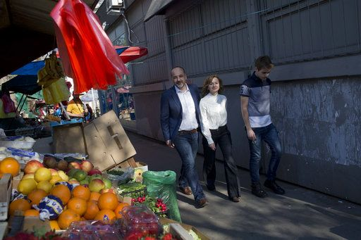 Sasa Jankovic, left, a Serbian presidential candidate, accompanied by his wife Slavica, center, walks past a fruit stall at a local market after he cast his ballot for the presidential elections in Belgrade, Serbia, Sunday, April 2, 2017. Voters in Serbia are casting ballots in a presidential election seen as a test of public support for populist Prime Minister Aleksandar Vucic and his autocratic rule.