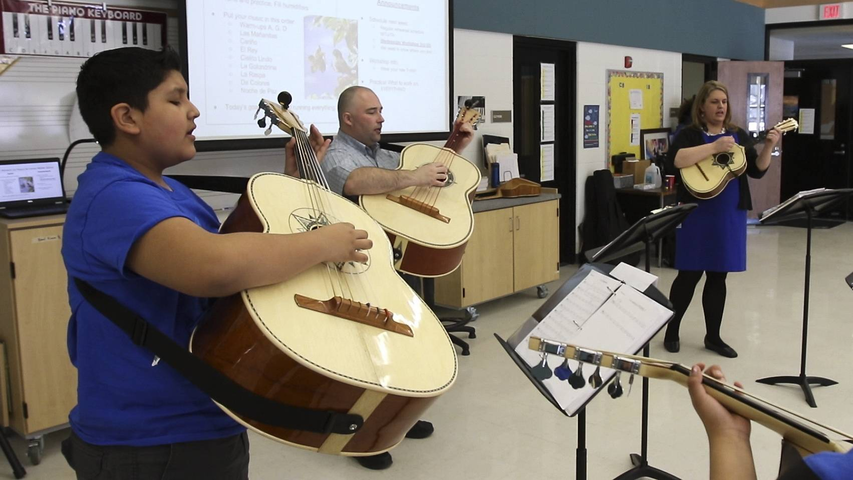 Left to right, Jordan Magna, 6th-grader, James Wallace, director, and Janet Sikma, orchestra director, lead the mariachi band at Leman Middle School in West Chicago.