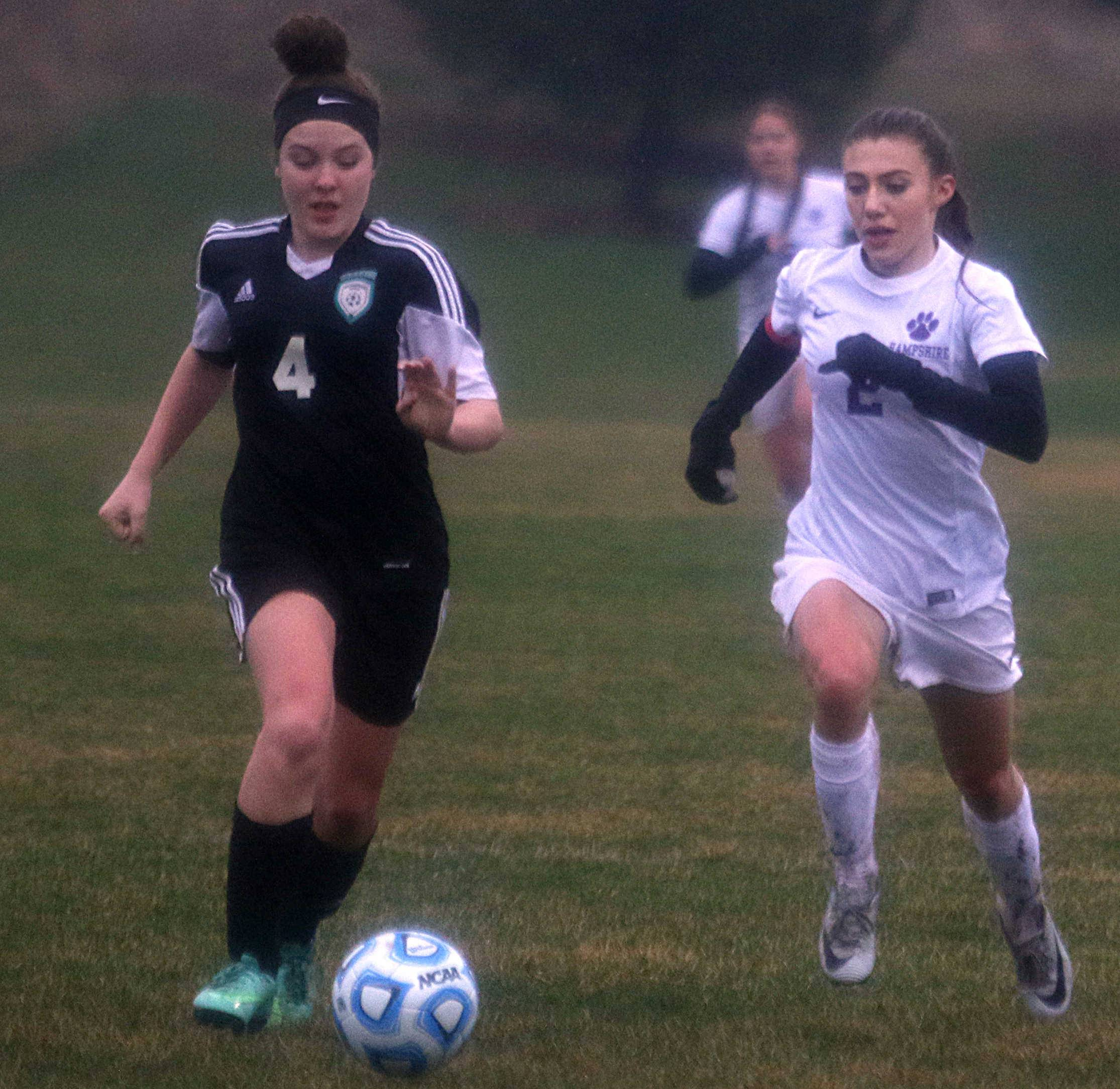 Hampshire's Morgan Heileman, right, races Woodstock North's Abigail Svitak for the ball during varsity girls soccer action at Hampshire Monday night.