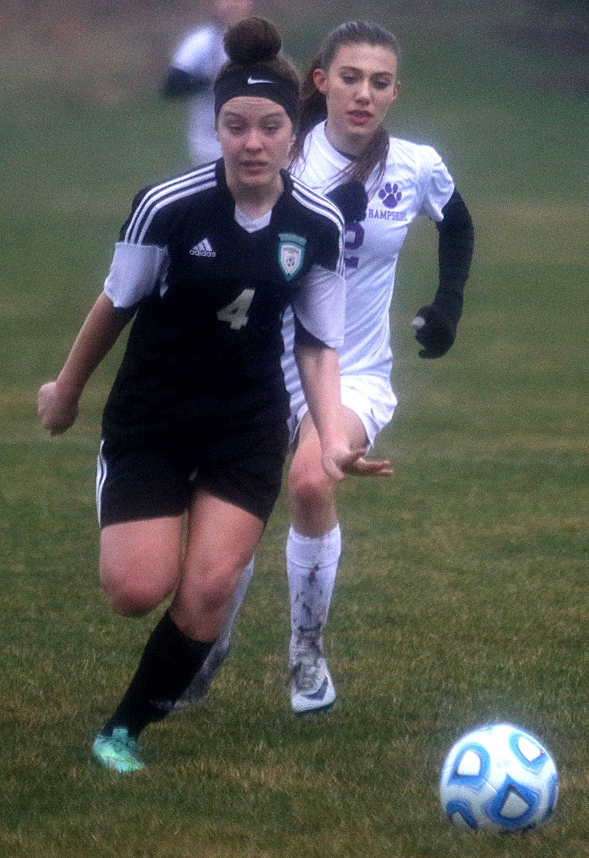 Hampshire's Morgan Heileman, back, races Woodstock North's Abigail Svitak, front, for the ball during varsity girls soccer action at Hampshire Monday night.