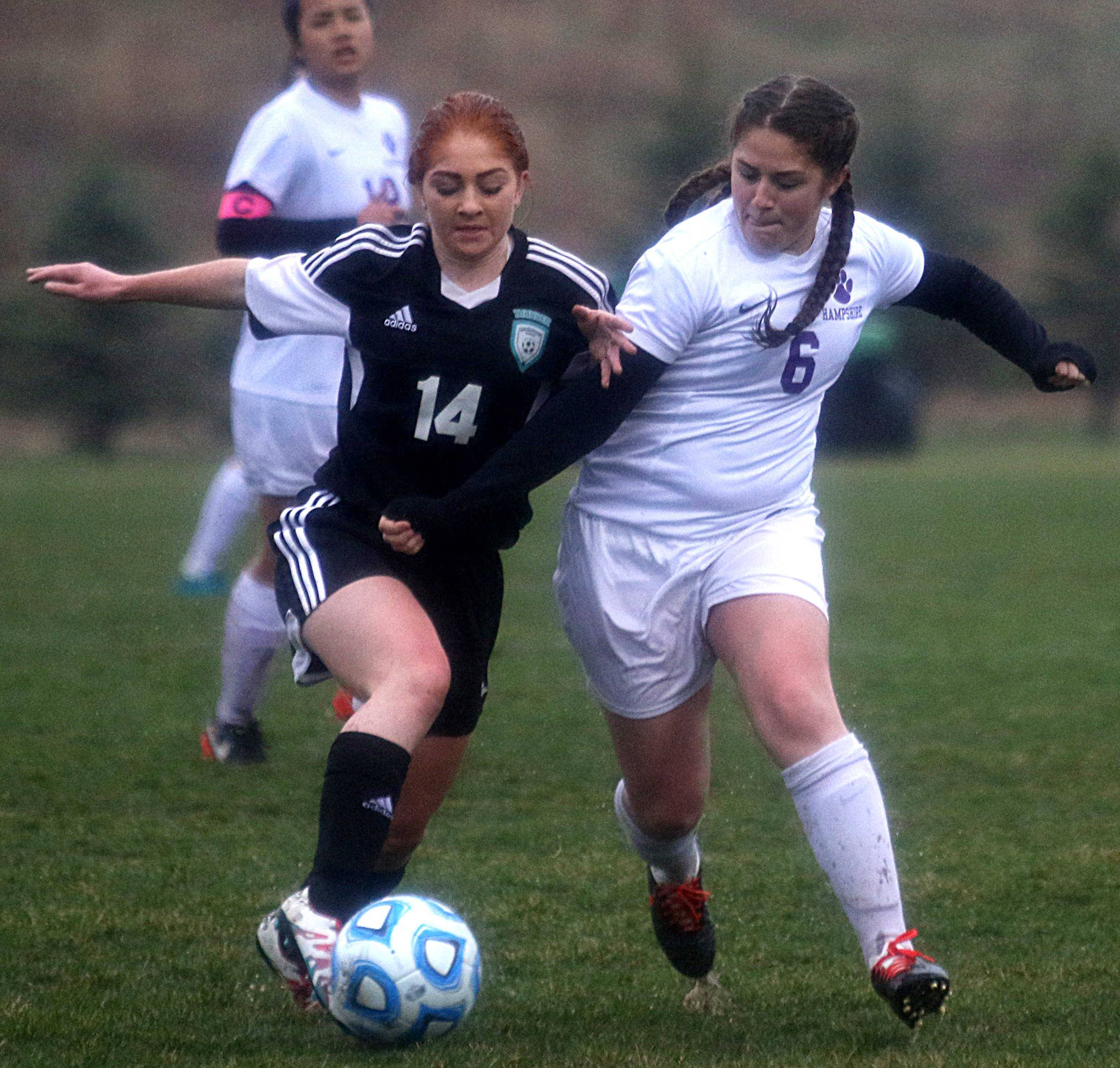 Hampshire's Sydney James, right, races Woodstock North's Anastasia Mazzanti for the ball during varsity girls soccer action at Hampshire Monday night.