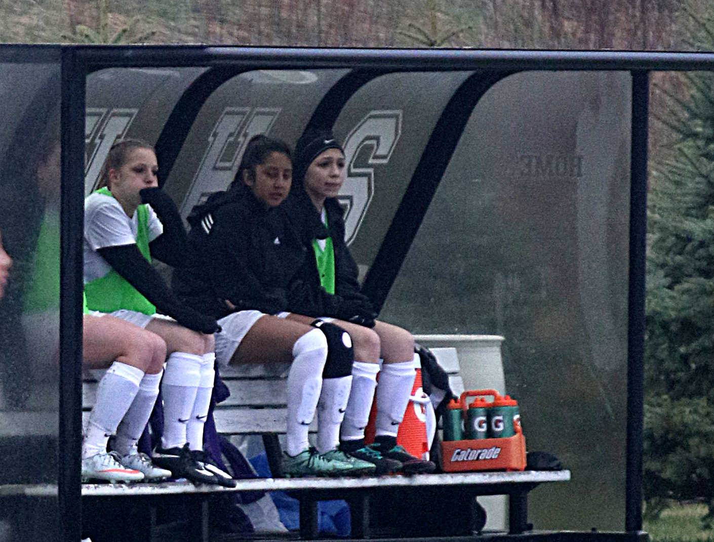 Hampshire players on the bench try to stay dry as the Whip-Purs play Woodstock North during varsity girls soccer action at Hampshire Monday night.
