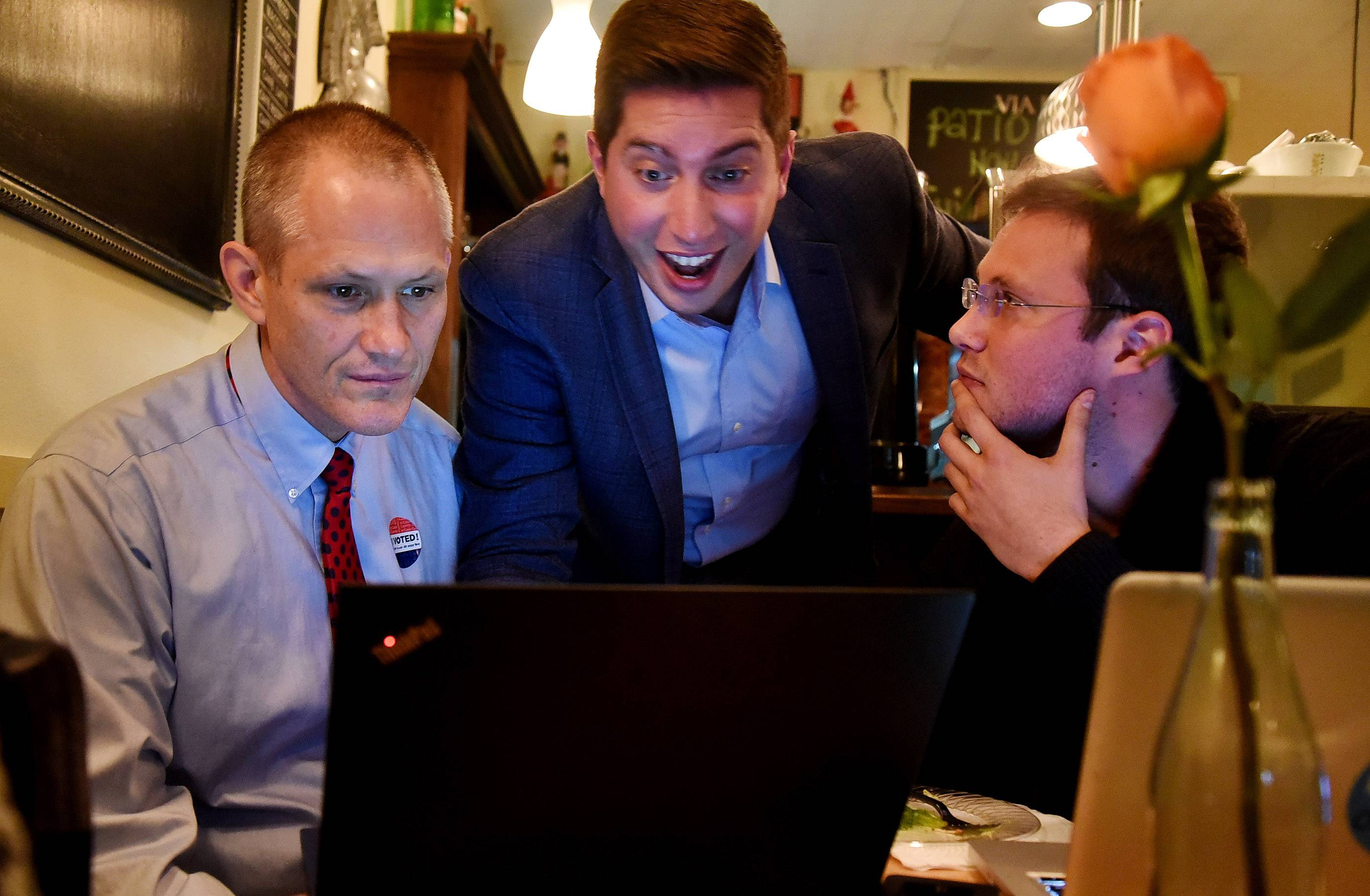 Des Plaines Mayor Matt Bogusz, along with campaign volunteer Tom Stettner, left, and campaign manager Matt Luchins look at their winning results at the Via Roma restaurant in Des Plaines.