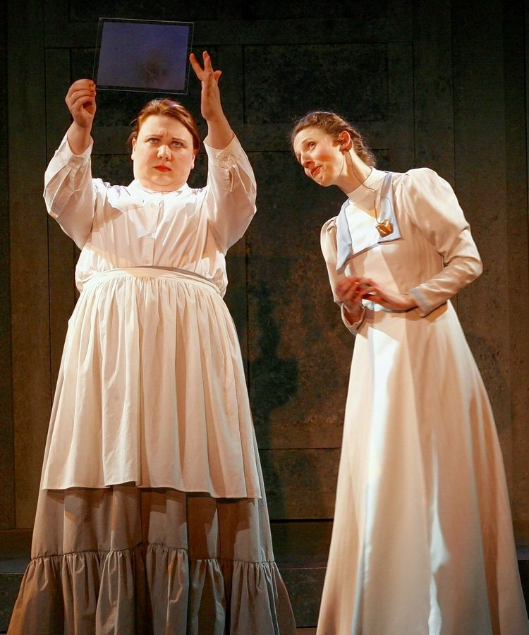 "Early 20th-century astronomer Henrietta Leavitt (Cassandra Bissell), right, describes to her sister Margaret (Hayley Rice) how she and her fellow ""human computers"" catalog the stars in First Folio Theatre's production of ""Silent Sky."""