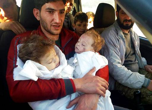 A father bids farewell to twin babies after Syria attack