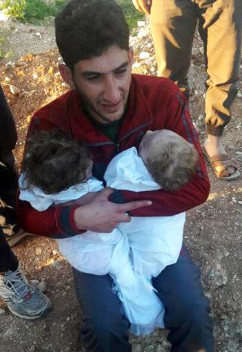 In this picture taken on Tuesday April 4, 2017, Abdul-Hamid Alyousef, 29, cries as he holds his twin babies who were killed during a suspected chemical weapons attack, in Khan Sheikhoun town, in the northern province of Idlib, Syria. Alyousef also lost his wife, two brothers, nephews and many other family members in the attack that claimed scores of his relatives. The death toll from a suspected chemical attack on a northern Syrian town rose to 72 on Wednesday as activists and rescue workers found more terrified survivors hiding in shelters near the site of the harrowing assault, one of the deadliest in Syria's civil war. (Alaa Alyousef via AP)