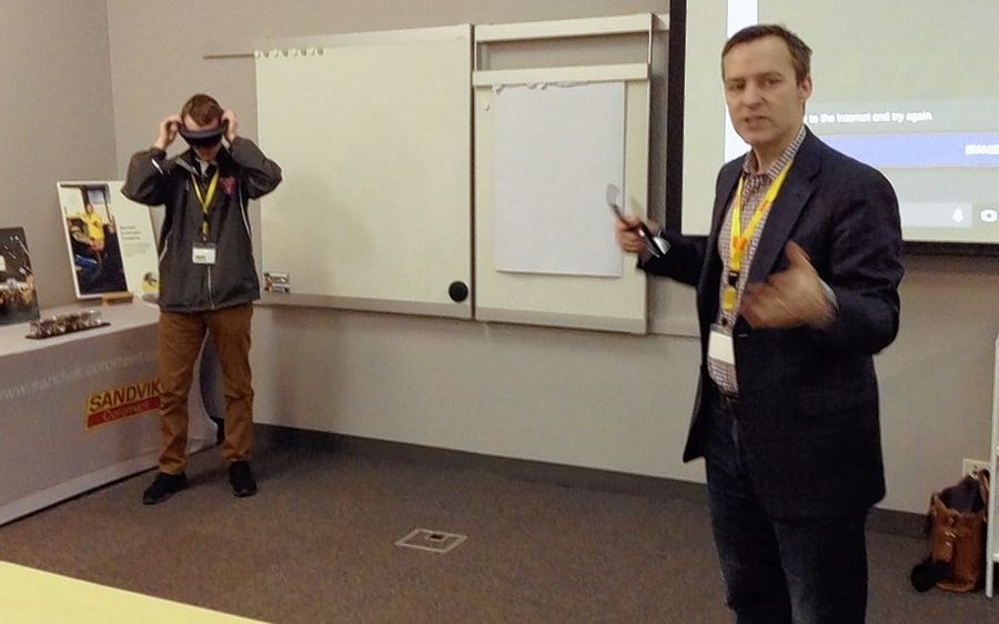 "Paul Edlund, right, chief technologist for Microsoft Midwest, explains the ""augmented reality"" of the Microsoft HoloLens to students from Palatine and Schaumburg high schools Friday. Palatine senior Matt Davis uses it to see a 3-D hologram of a human anatomical model at the Sandvik Cormorant training center in Schaumburg."