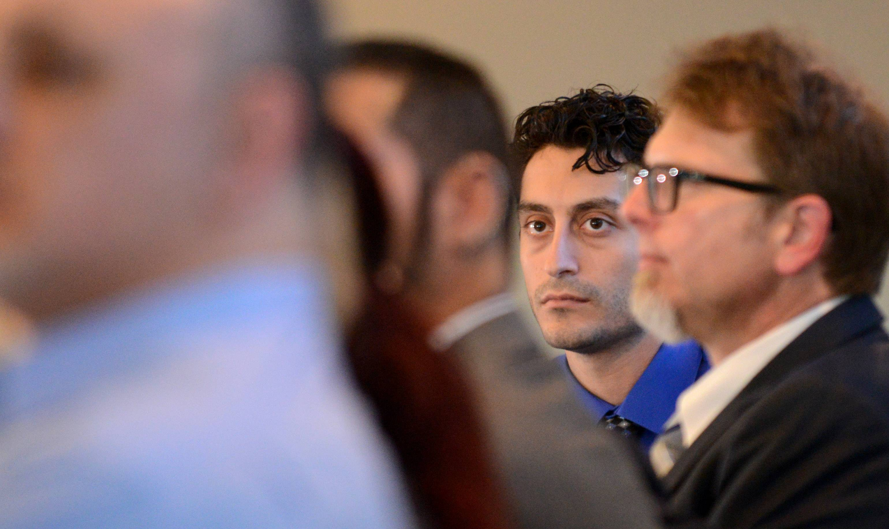 Mario Casciaro, center, listens as he's introduced at a 2015 event featuring stories of wrongful convictions hosted by the Kane County Public Defender's Office.