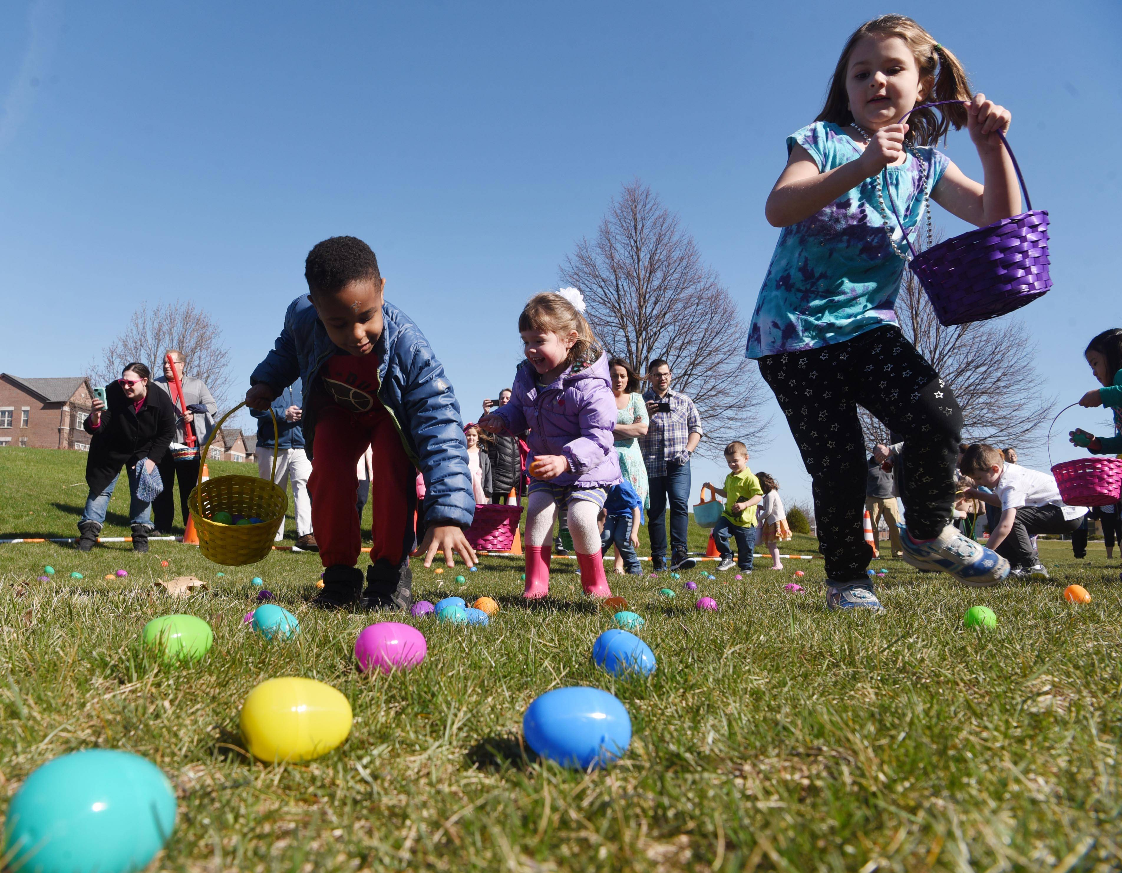 Justin Sitati, 4, left, and Evelyn DeAngelis, 5, right, both of Vernon Hills are among a group of children gathering Easter eggs during the Hoppin' Holiday Hunt at the Sullivan Community Center in Vernon Hills Saturday.