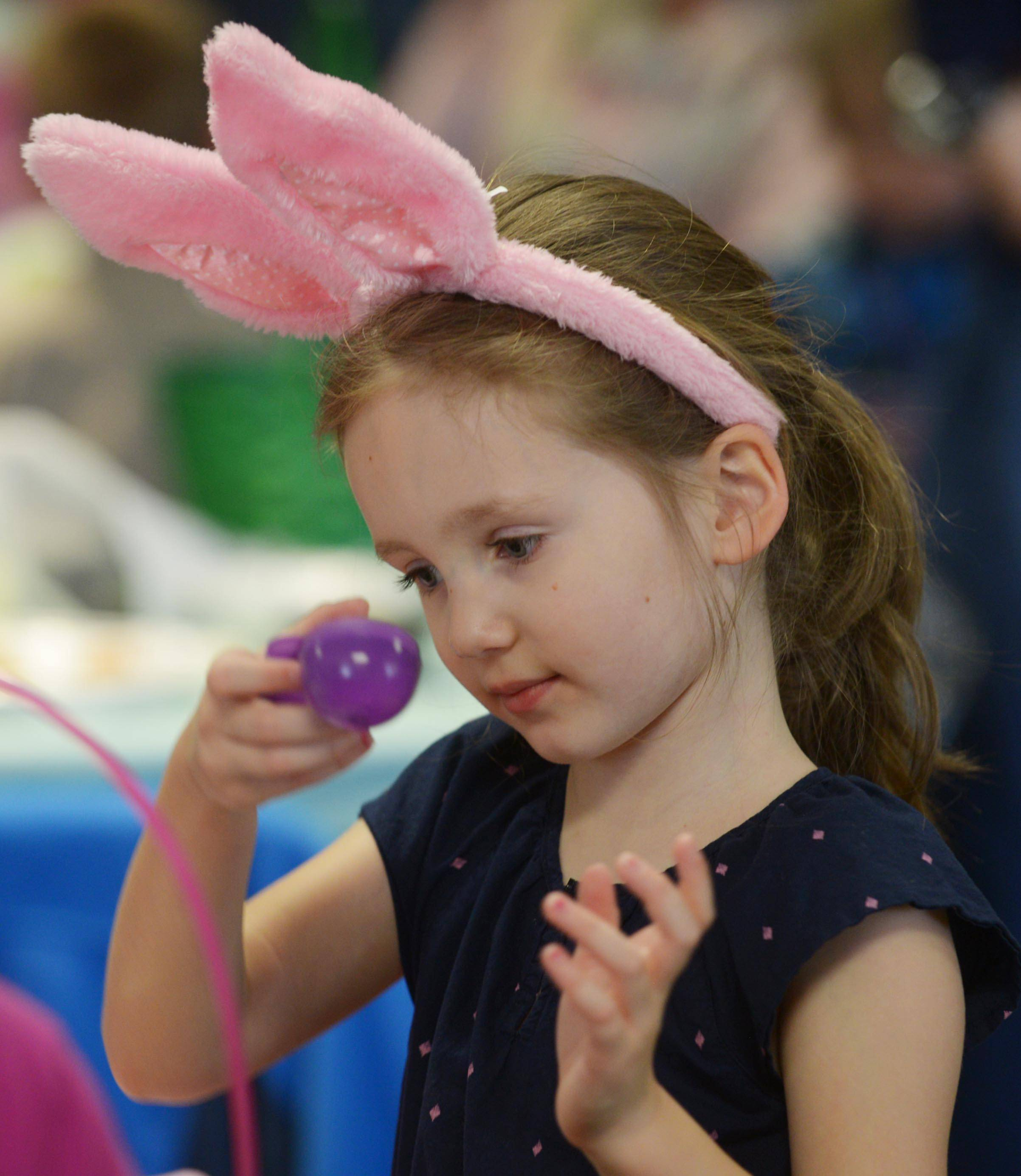 Adelaide Freeborn, 4, of Vernon Hills looks inside an Easter egg during the Hoppin' Holiday Hunt at the Sullivan Community Center in Vernon Hills Saturday.