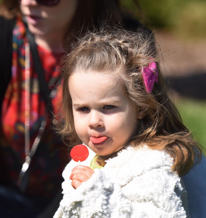 Malia Thorson, 2½, enjoys a lollipop prize Saturday at the Mooseheart Easter egg hunt in North Aurora. Her family is from Geneva.