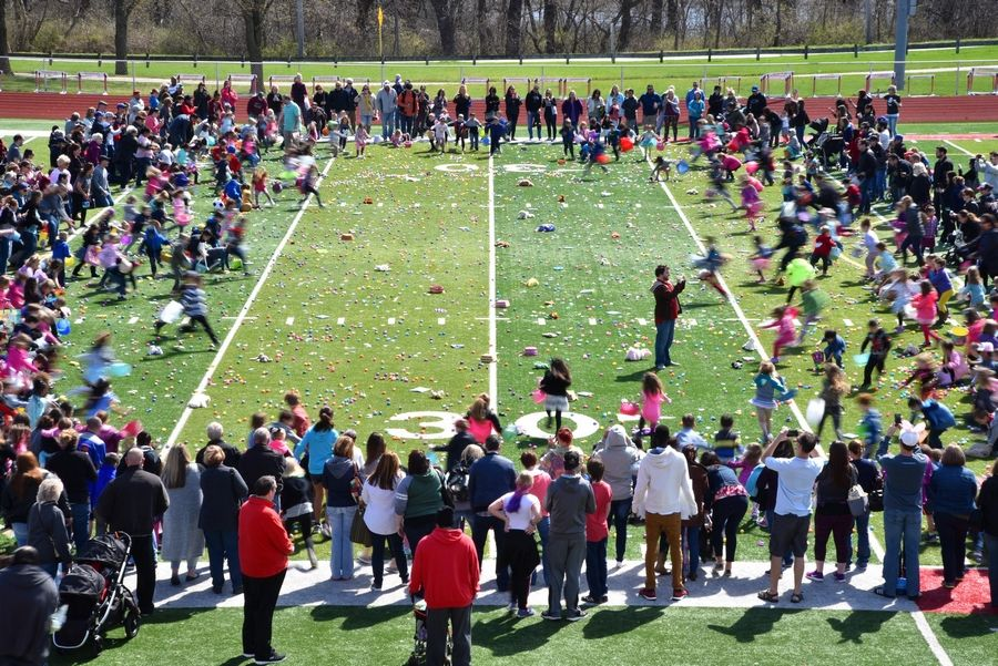 Children rush from the edges to collect toys plastic eggs filled with candy Saturday at the Mooseheart Easter egg hunt in North Aurora.