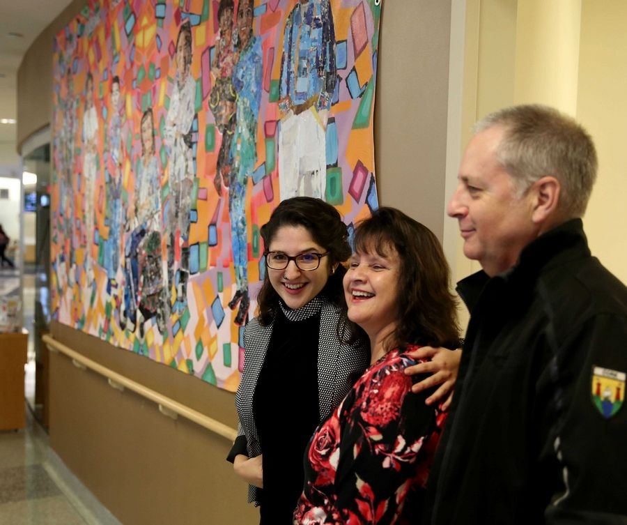 "Artist Hallie Morrison poses for pictures with parents Nohra and Bill Morrison of Algonquin after Hallie's mural was unveiled at Advocate Sherman Hospital in Elgin Monday. The hospital's diversity and inclusion council unveiled a multicultural, globe-trotting ""welcome mural"" in its main lobby Monday night. The mural incorporates the community's various cultures; the hospital's five values of compassion, stewardship, equality, partnership, and excellence; and the word ""welcome"" in various languages. It has been in Thailand, where local youths helped artist Hallie Morrison work on the project. The two-year project included a partnership with Side Street Studio Arts in Elgin."