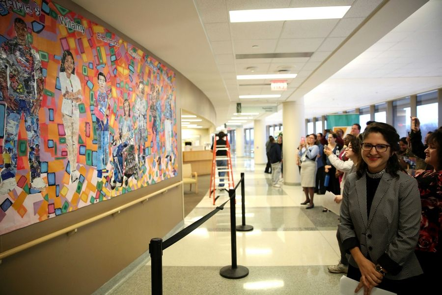 "Advocate Sherman Hospital's diversity and inclusion council unveiled a multicultural, globe-trotting ""welcome mural"" in its main lobby Monday night. The mural incorporates the community's various cultures; the hospital's five values of compassion, stewardship, equality, partnership, and excellence; and the word ""welcome"" in various languages. It has been in Thailand, where local youths helped artist Hallie Morrison work on the project. The two-year project included a partnership with Side Street Studio Arts in Elgin."