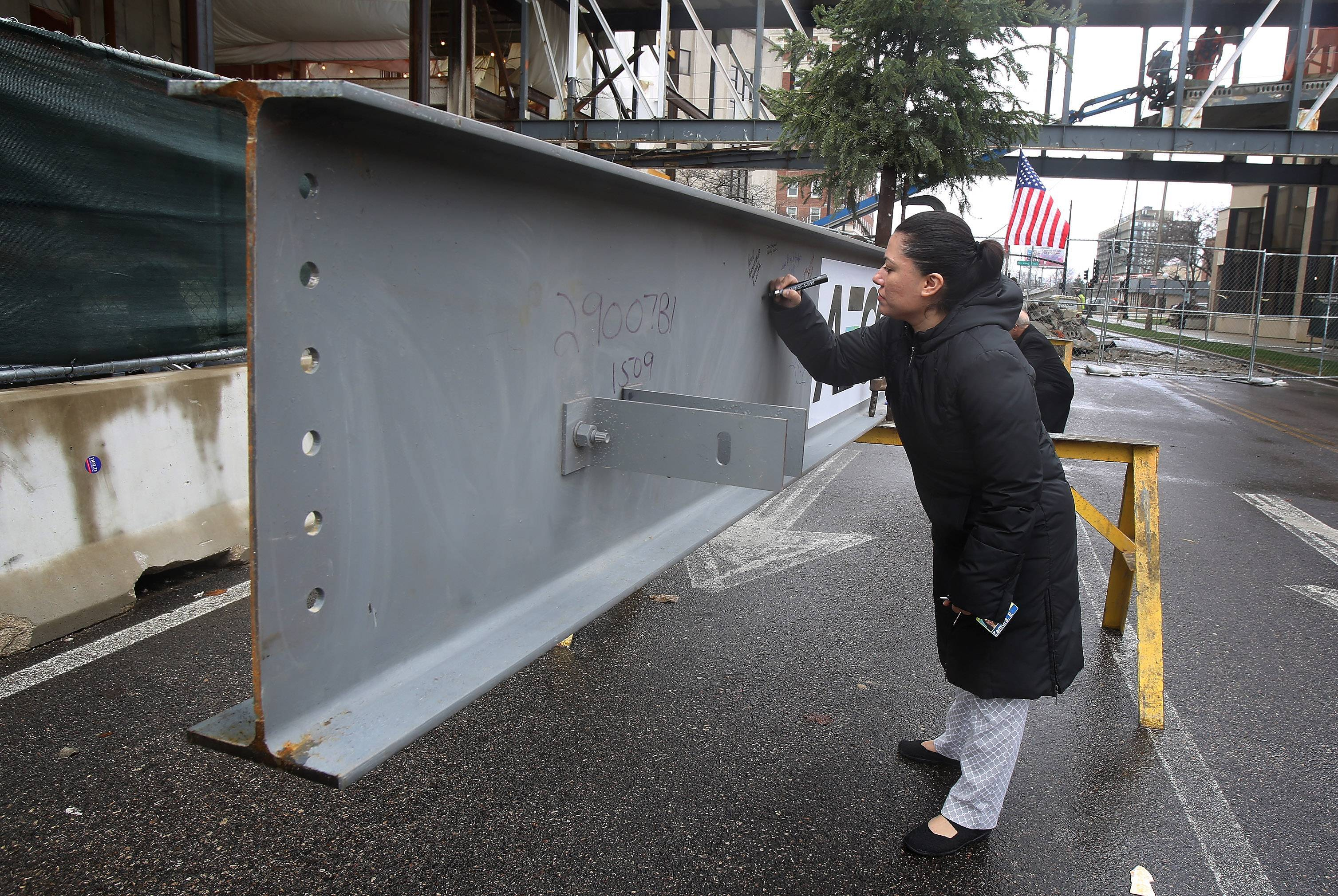 Elisa Gomez of Gurnee signs the final beam Tuesday of a new tower being built for the $112 million Lake County courthouse expansion in Waukegan. The beam will be raised to the top of the building Wednesday.