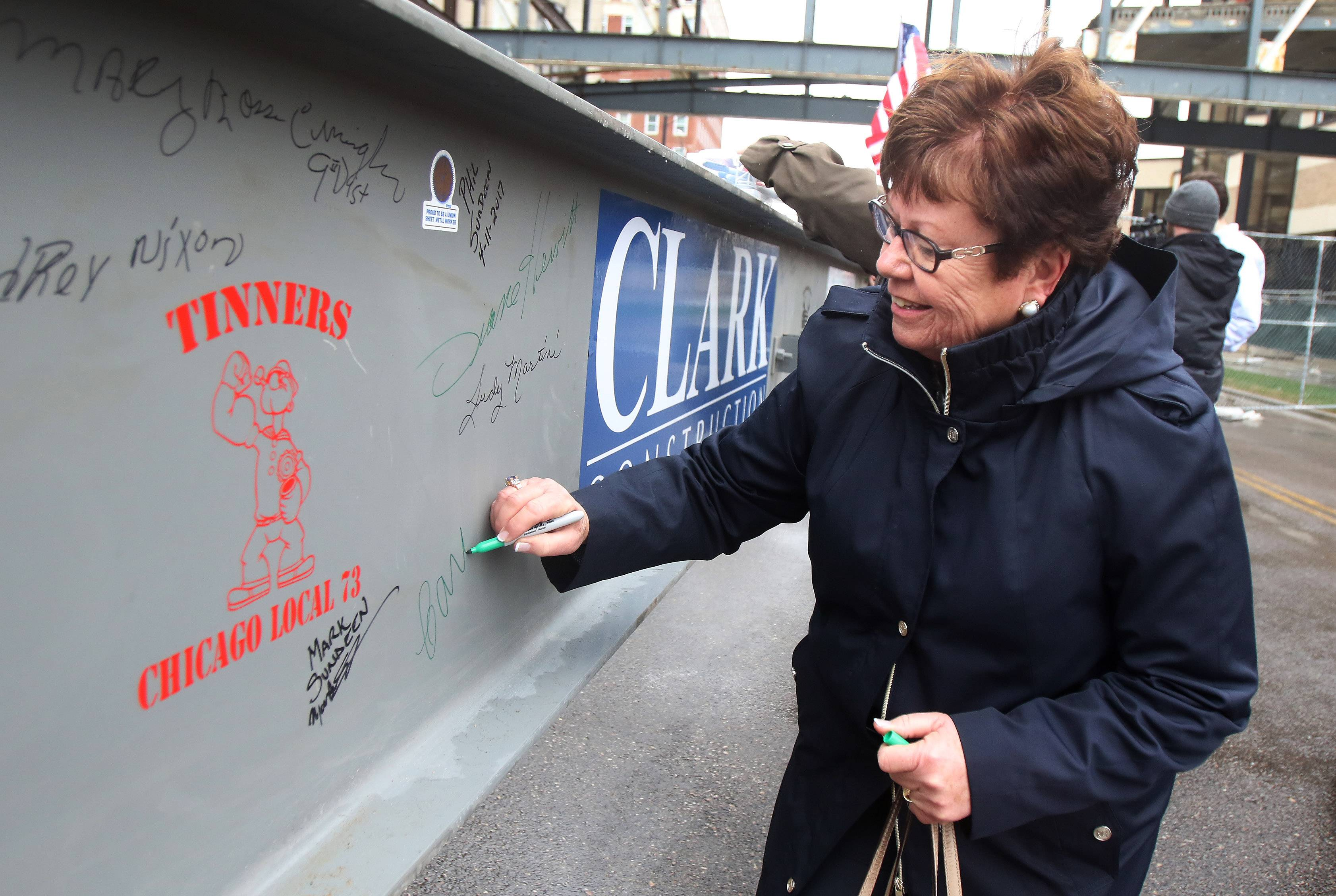 Lake County Board member Carol Calabresa signs the final beam Tuesday of a new tower being built for the $112 million Lake County courthouse expansion in Waukegan. The beam will be raised to the top of the building Wednesday.